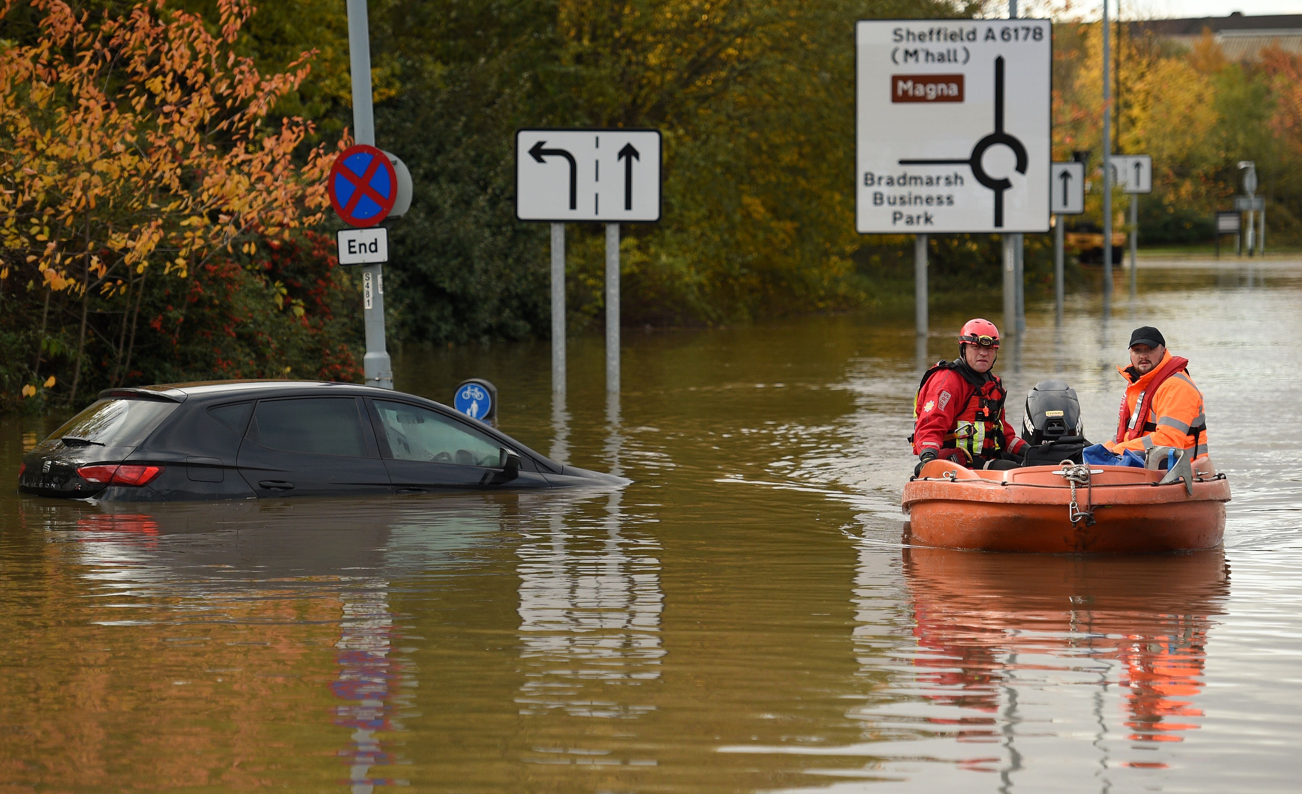 Members of the Fire and Rescue service make their way through flood water covering a flooded road in Rotherham.