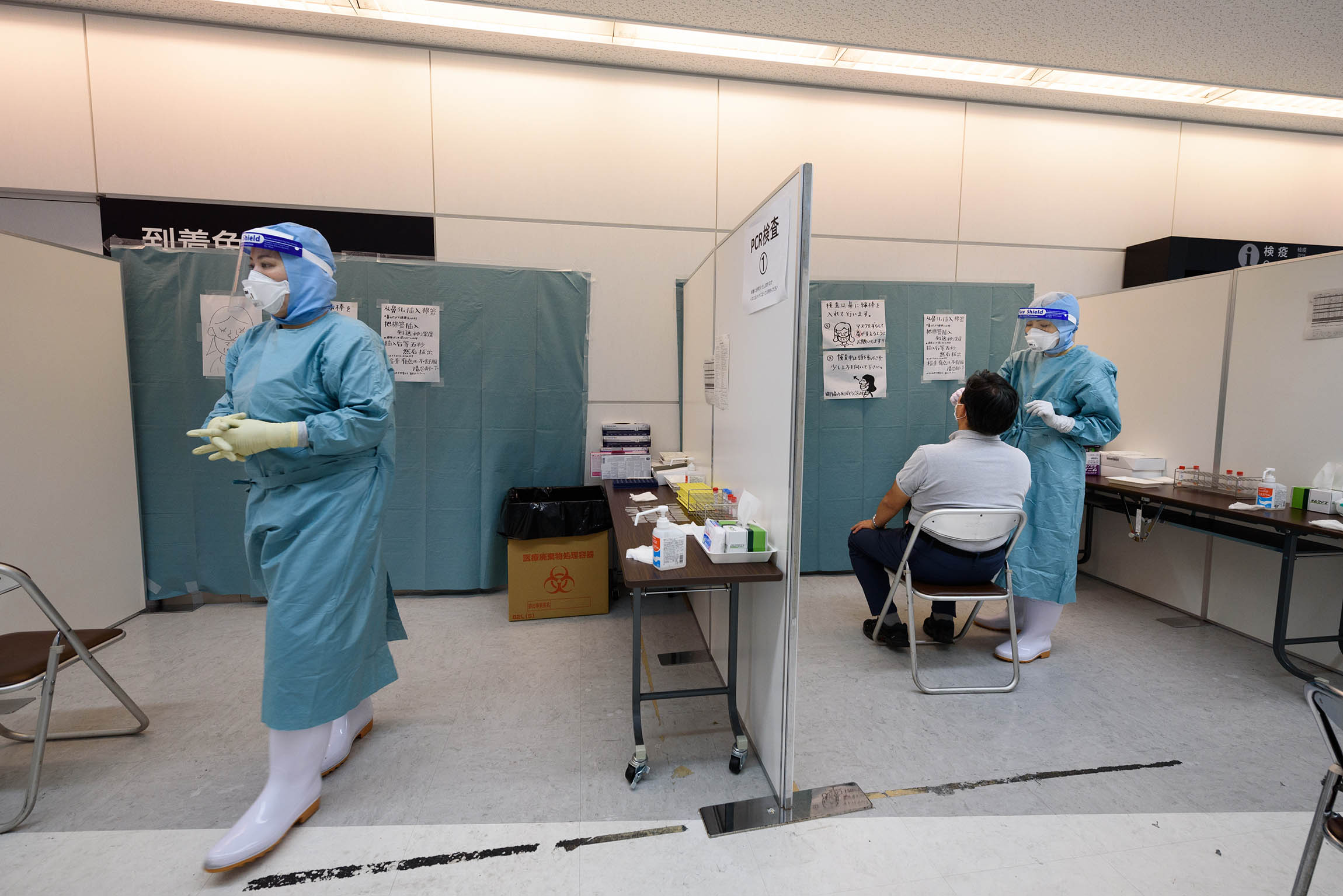 A medical worker collects a nasal swab from an arrival passenger to test for Covid-19 at a polymerase chain reaction (PCR) testing site in Narita, Chiba Prefecture, Japan, on Sunday, July 19, 2020.