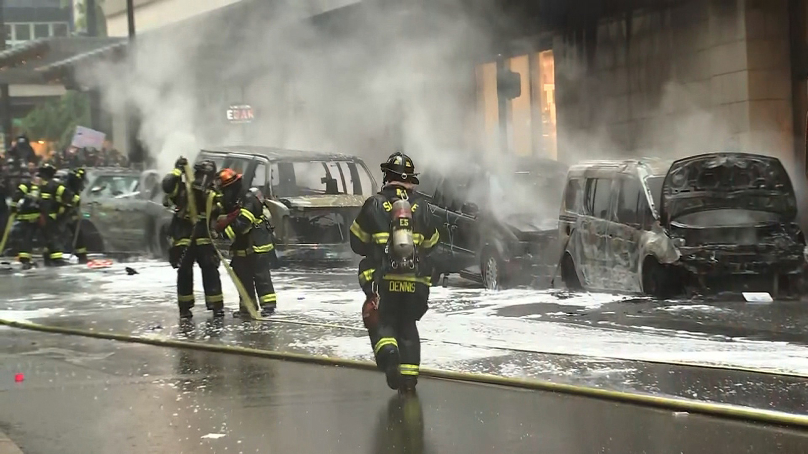 Firefighters collect the hose on the street after extinguishing car fires set by protesters in Seattle, on May 30.