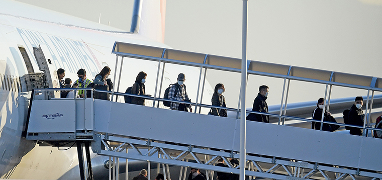 Travelers wearing masks exit off of China Airlines flight 24 at Ontario International Airport after arriving from Taipei, Taiwan Tuesday January 28.
