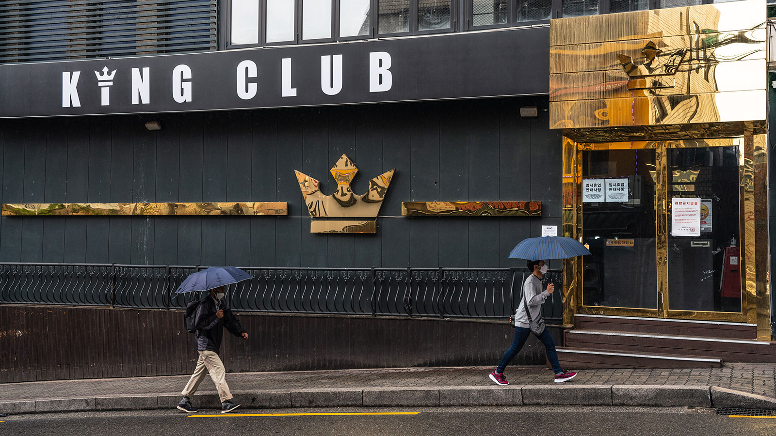 People wearing masks walk by a closed nightclub in the Itaewon district of Seoul.