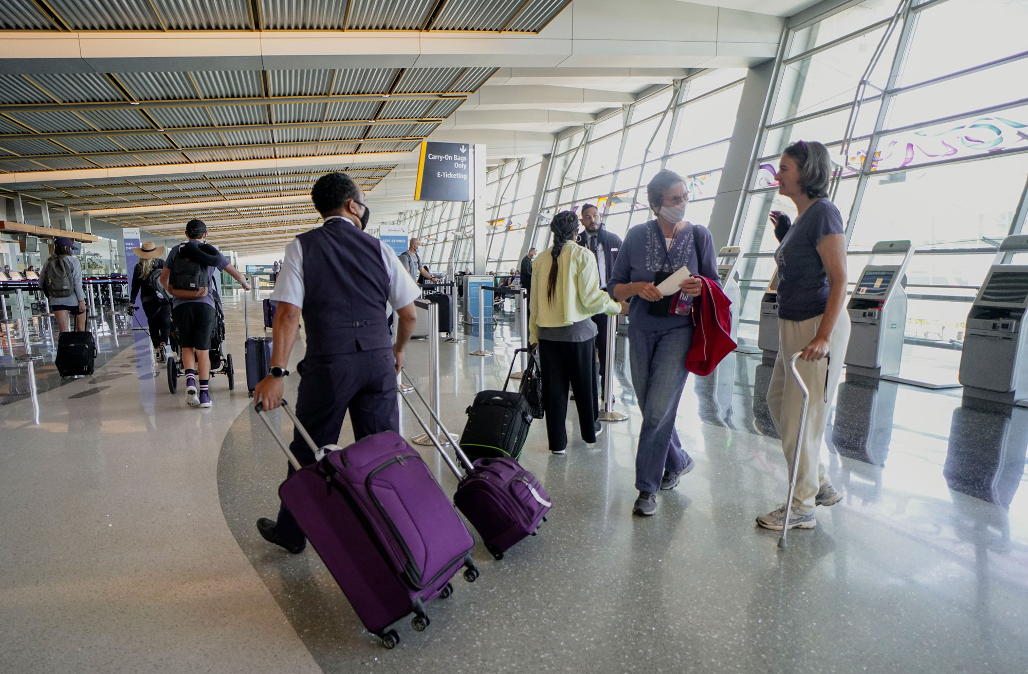 Passengers check in for their flights at San Diego International Airport on May 20 in San Diego.