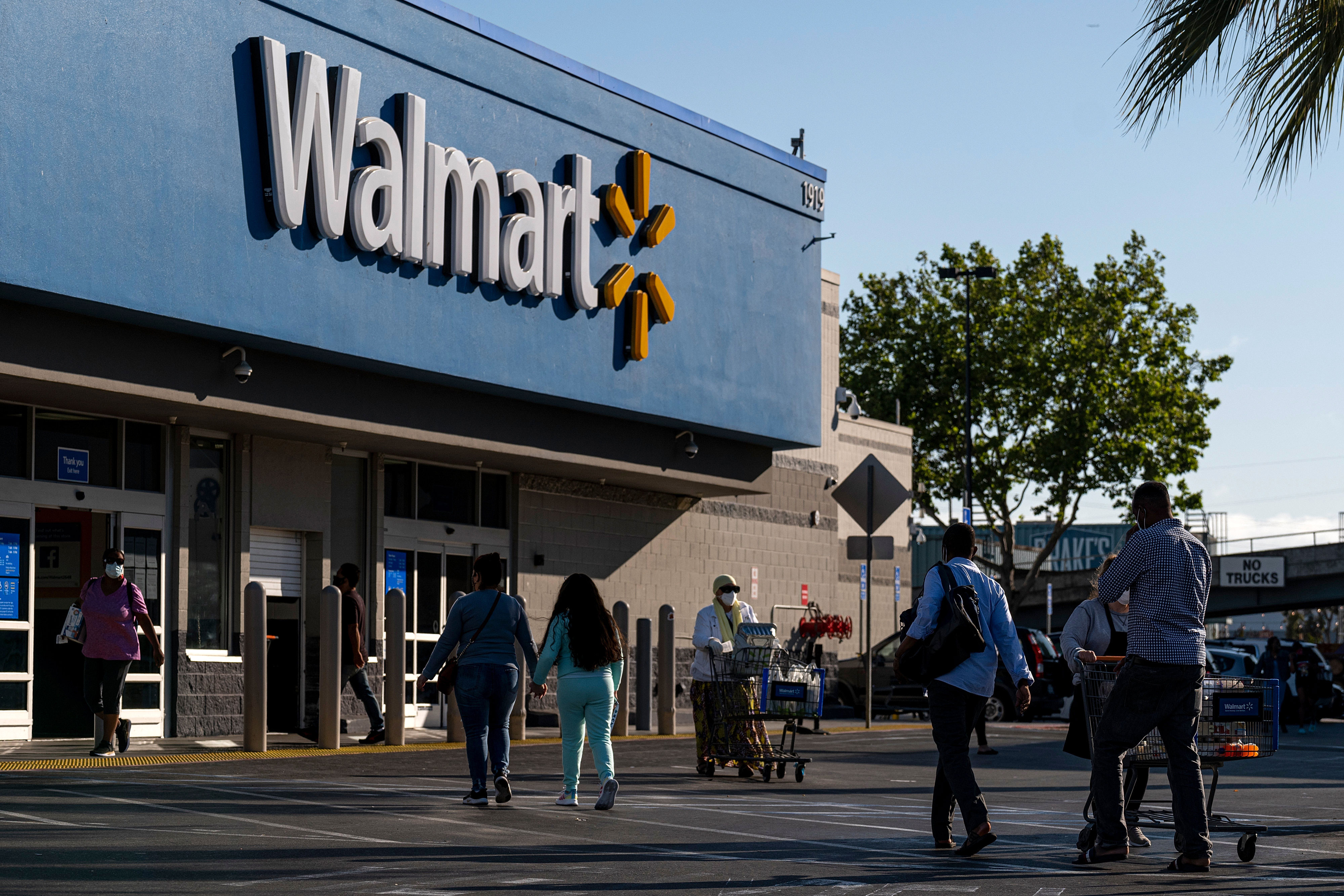 People walk in front of a Walmart store in San Leandro, California, on May 13.