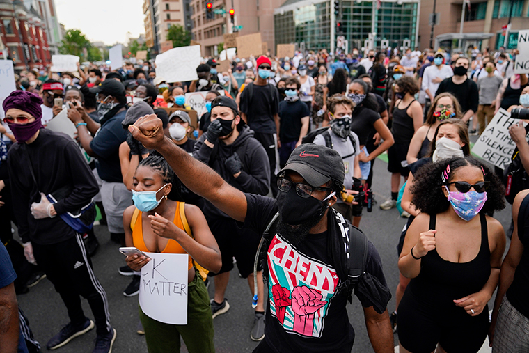 Demonstrators gather at the corner of 14th and U streets in Washington, Friday, May 29.