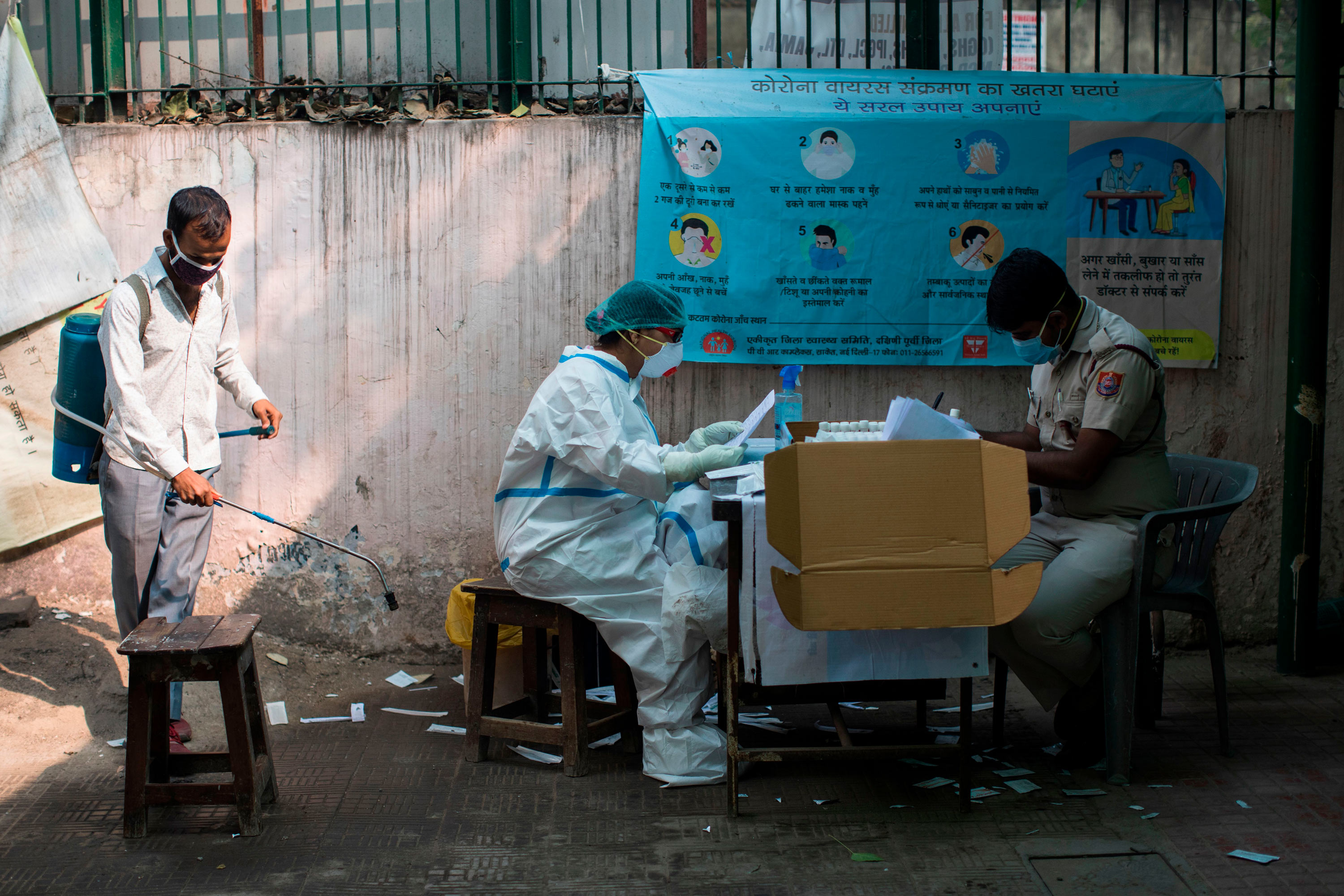 A medical worker along with a policeman sort out swab samples collected for Rapid Antigen Tests for Covid-19 at a dispensary in New Delhi on November 10.