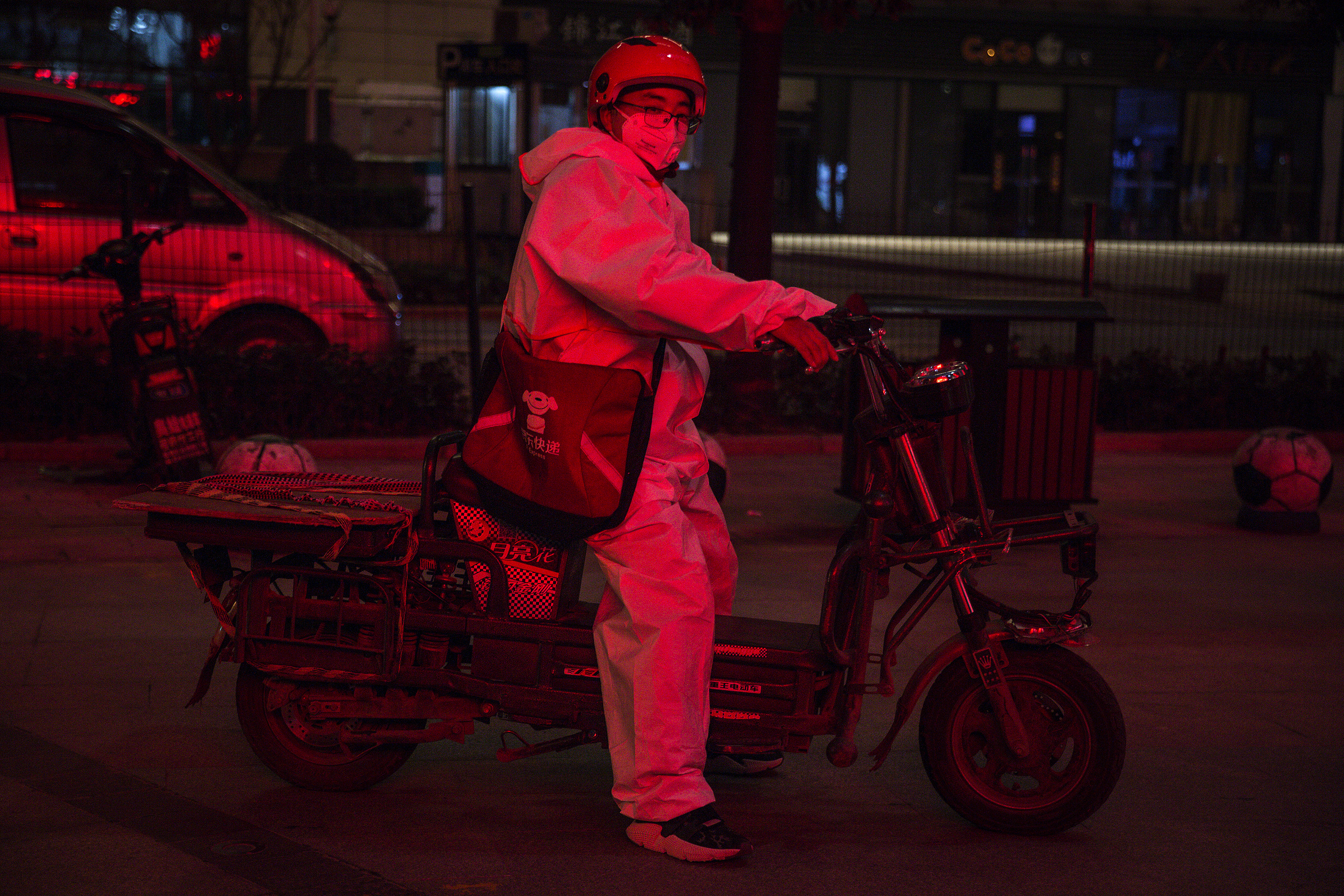 A delivery driver wears a protective mask and suit as he delivers packages on Saturday in Wuhan.