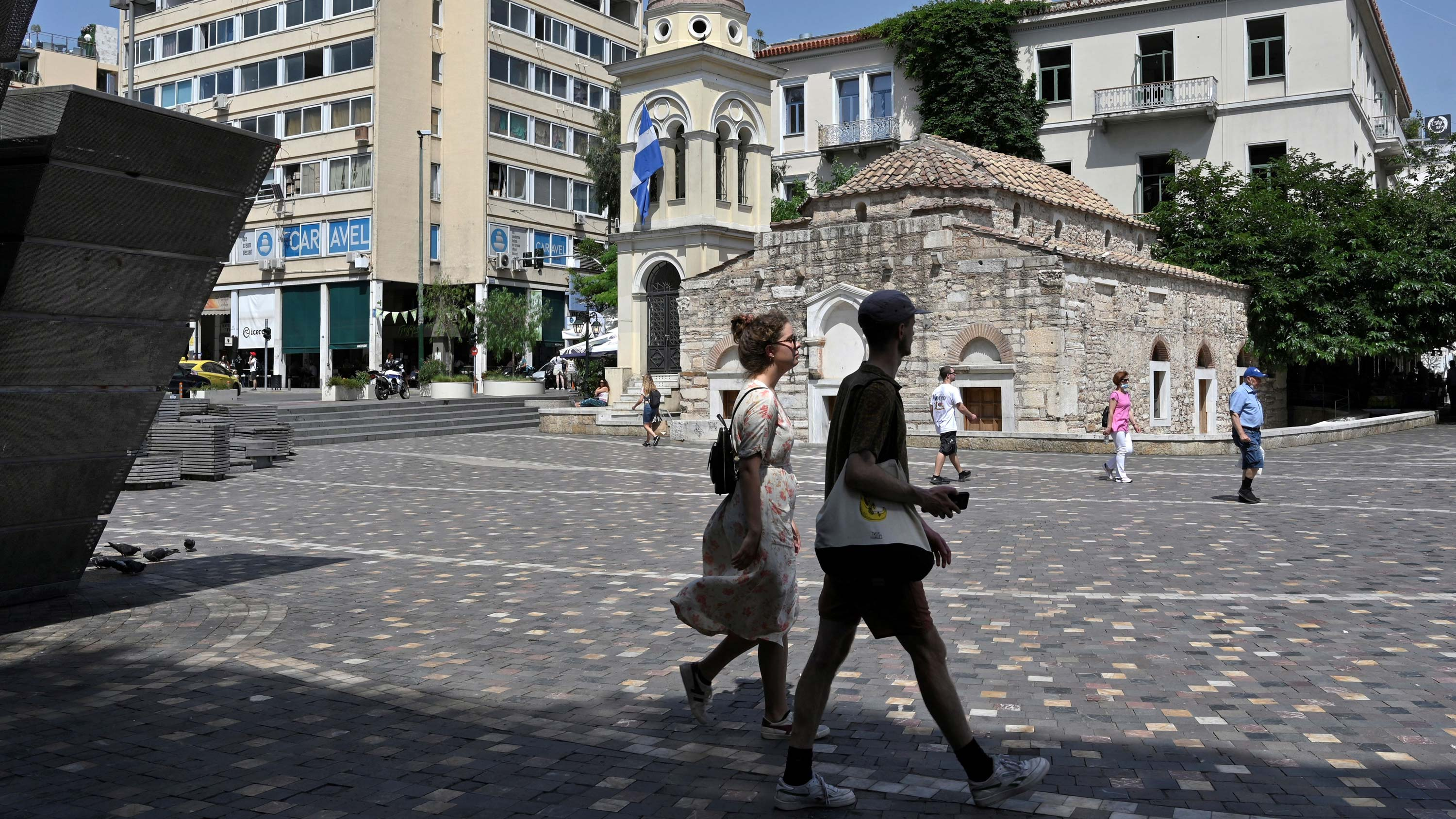 People walk at central Athens square on June 24.