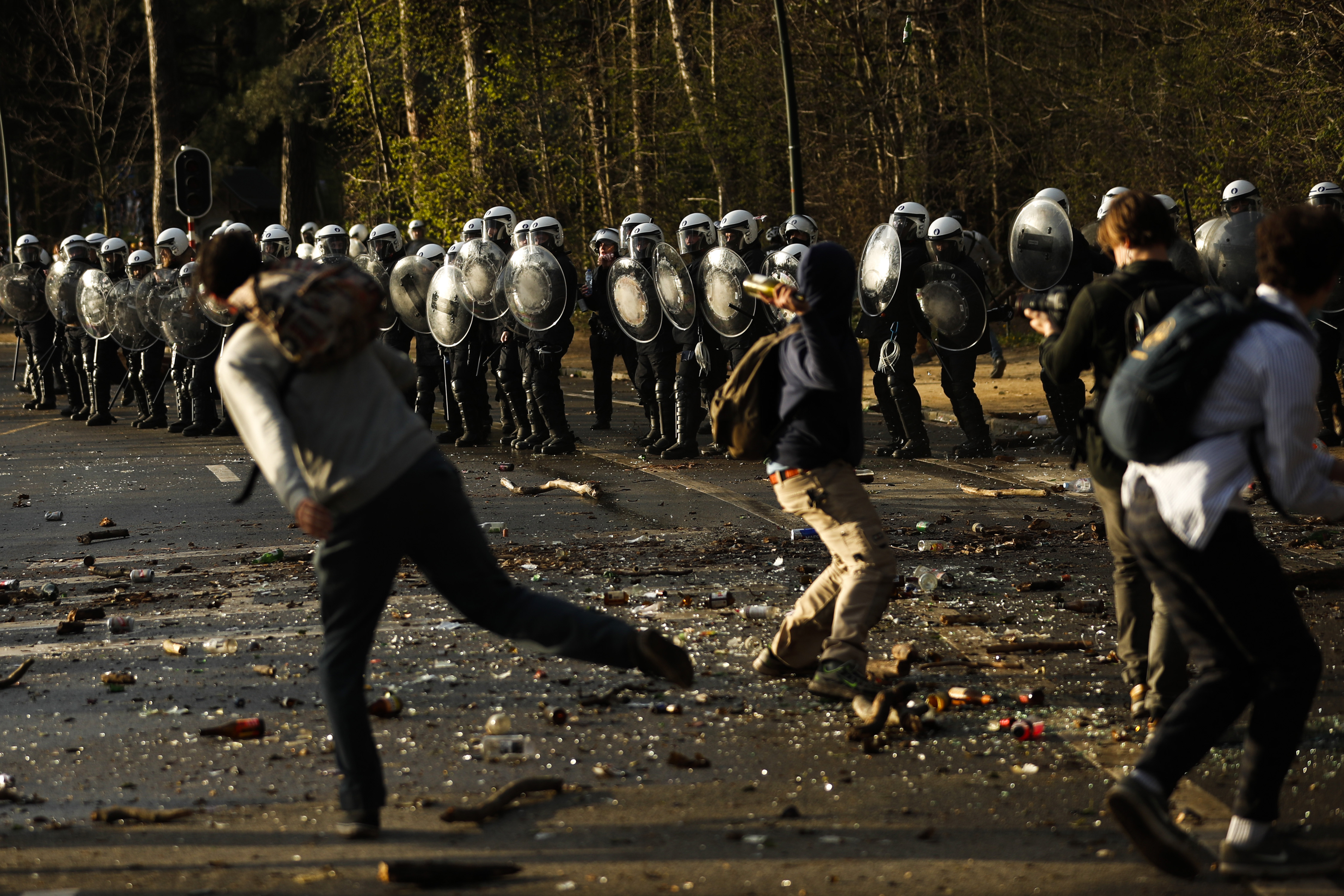 People throw objects towards police in Bois de la Cambre park in Brussels, as clashes broke out following an  unauthorized event in violation of coronavirus restrictions, on April 1.