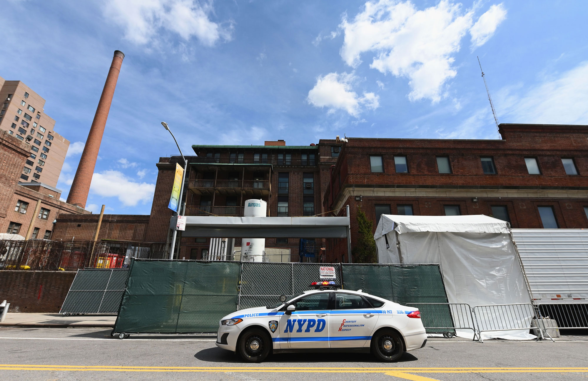 A NYPD car is parked in front of a refrigerated truckoutside of the Brooklyn Hospital on April 1, in New York City.