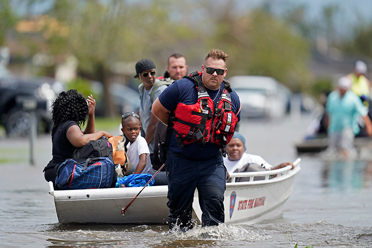 Members of the Louisiana State Fire Marshal's office rescue people from floodwaters in the aftermath of Hurricane Ida in New Orleans, Louisiana, Monday, August 30.