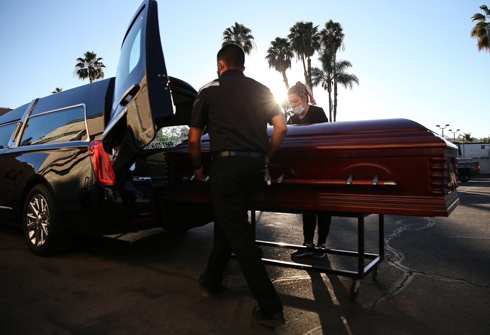 The casket of a person who died after contracting Covid-19 is loaded into a hearse in El Cajon, California, on January 15, 2021.