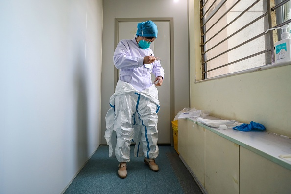 A doctor puts on a protective suit before entering the isolation ward at a hospital in Wuhan on January 30, 2020.