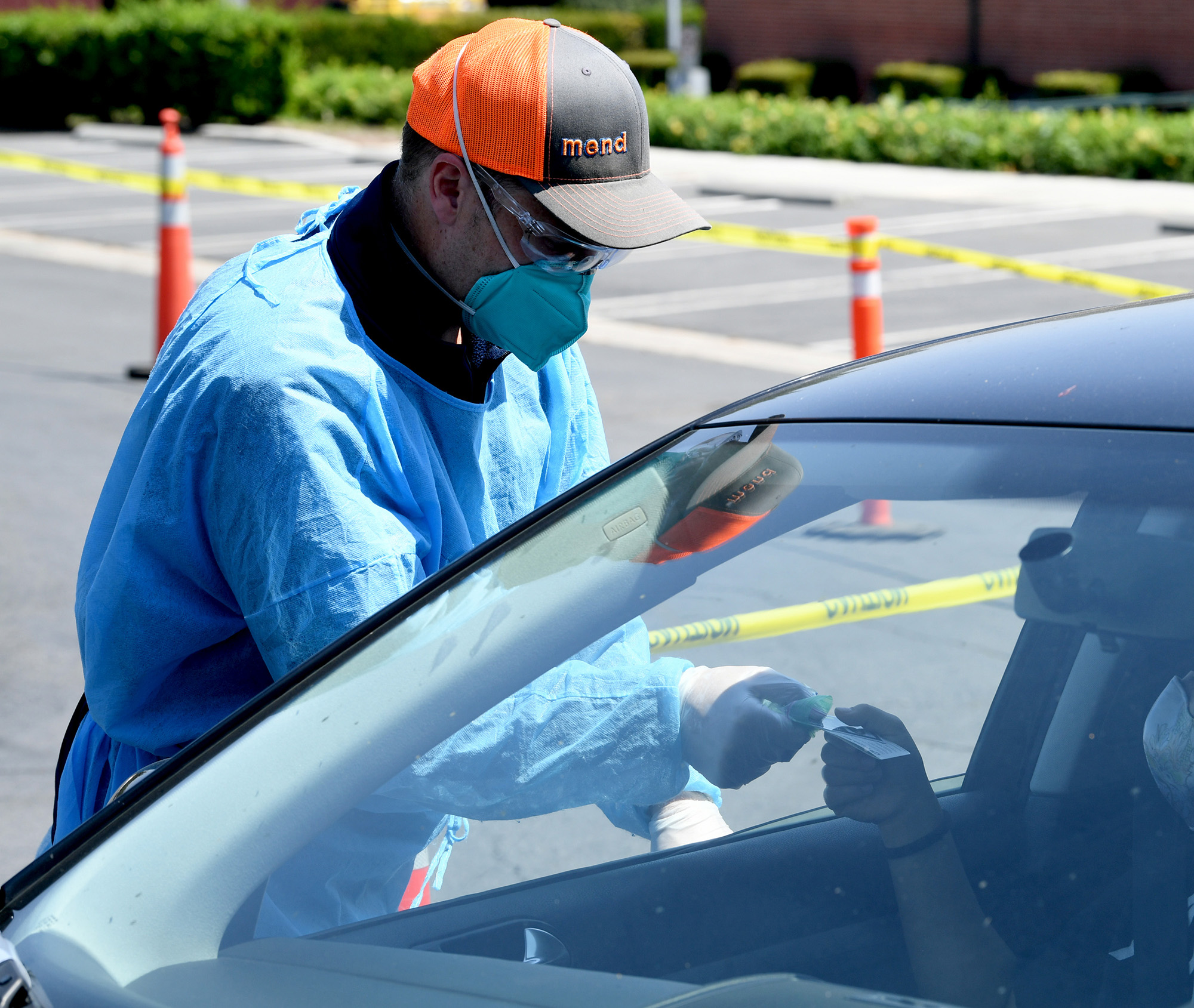 Mend Urgent Care workers perform drive-up COVID-19 testing on August 24, in Burbank, California.