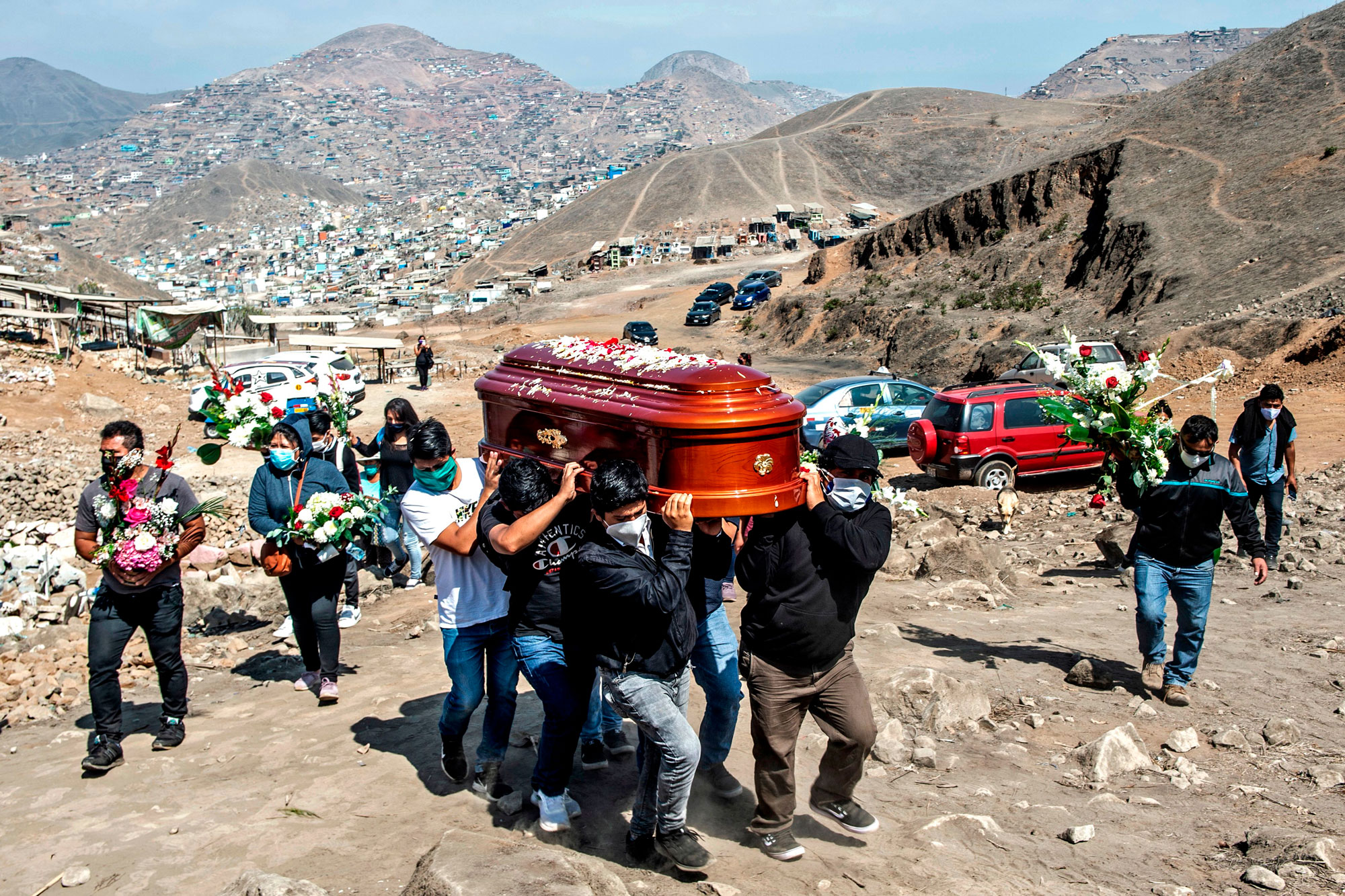People carry the coffin of a suspected coronavirus victim at the Nueva Esperanza cemetery, on the southern outskirts of Lima, Peru, on Saturday, May 30.