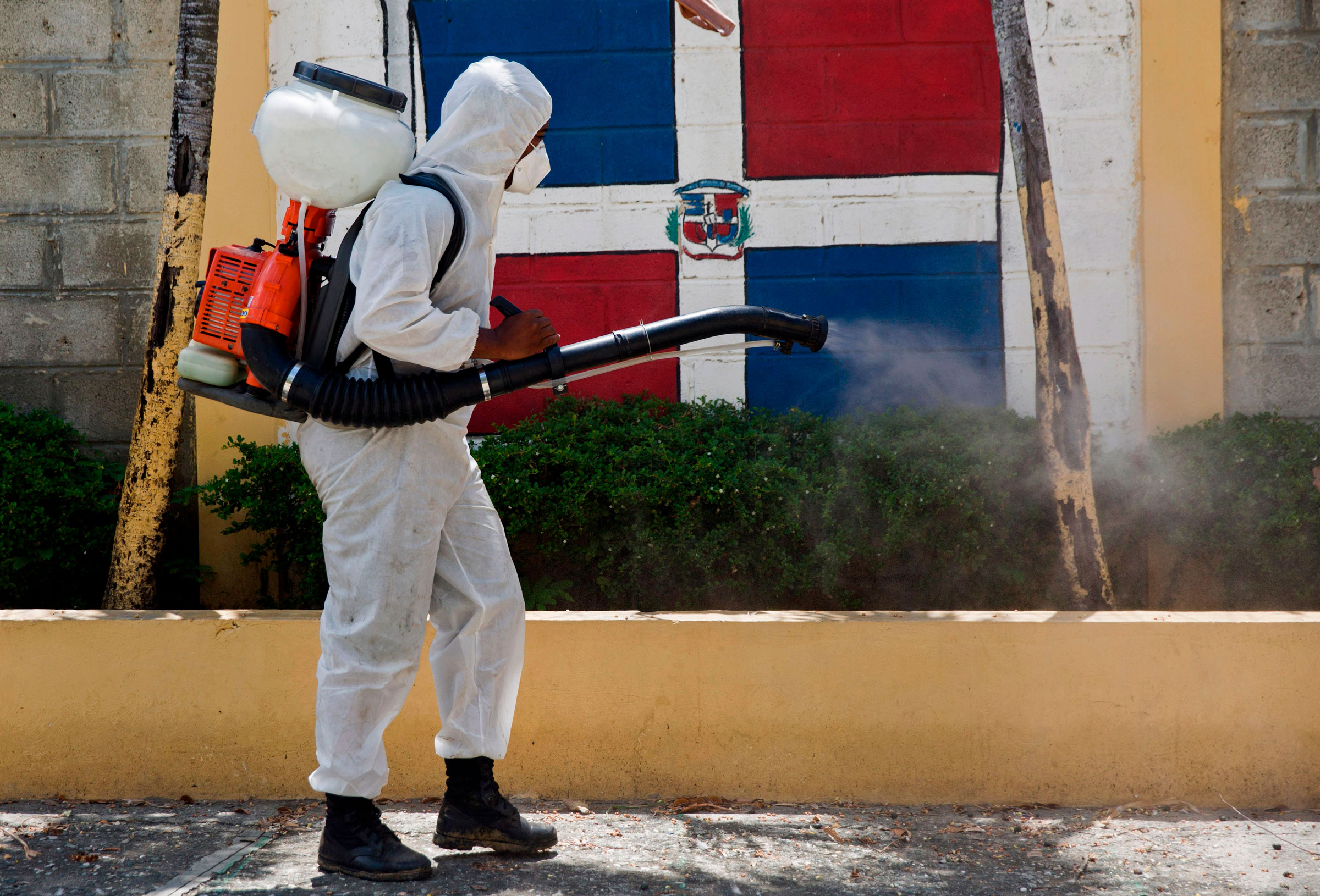 A worker fumigates an area of San Cristobal, Dominican Republic, in June.