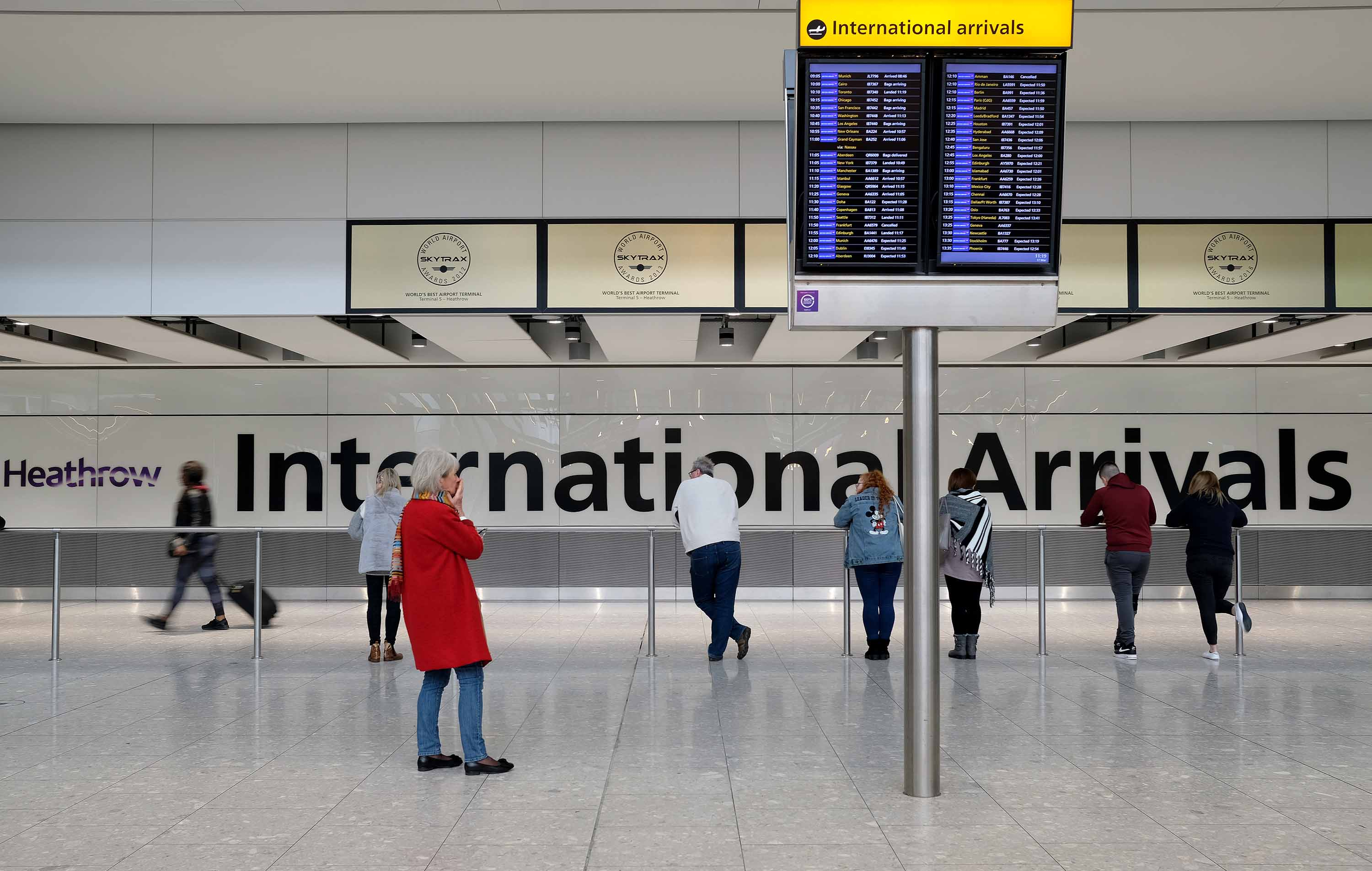 People wait for passengers at the International Arrivals hall in Heathrow Airport, in London, England, on March 17.