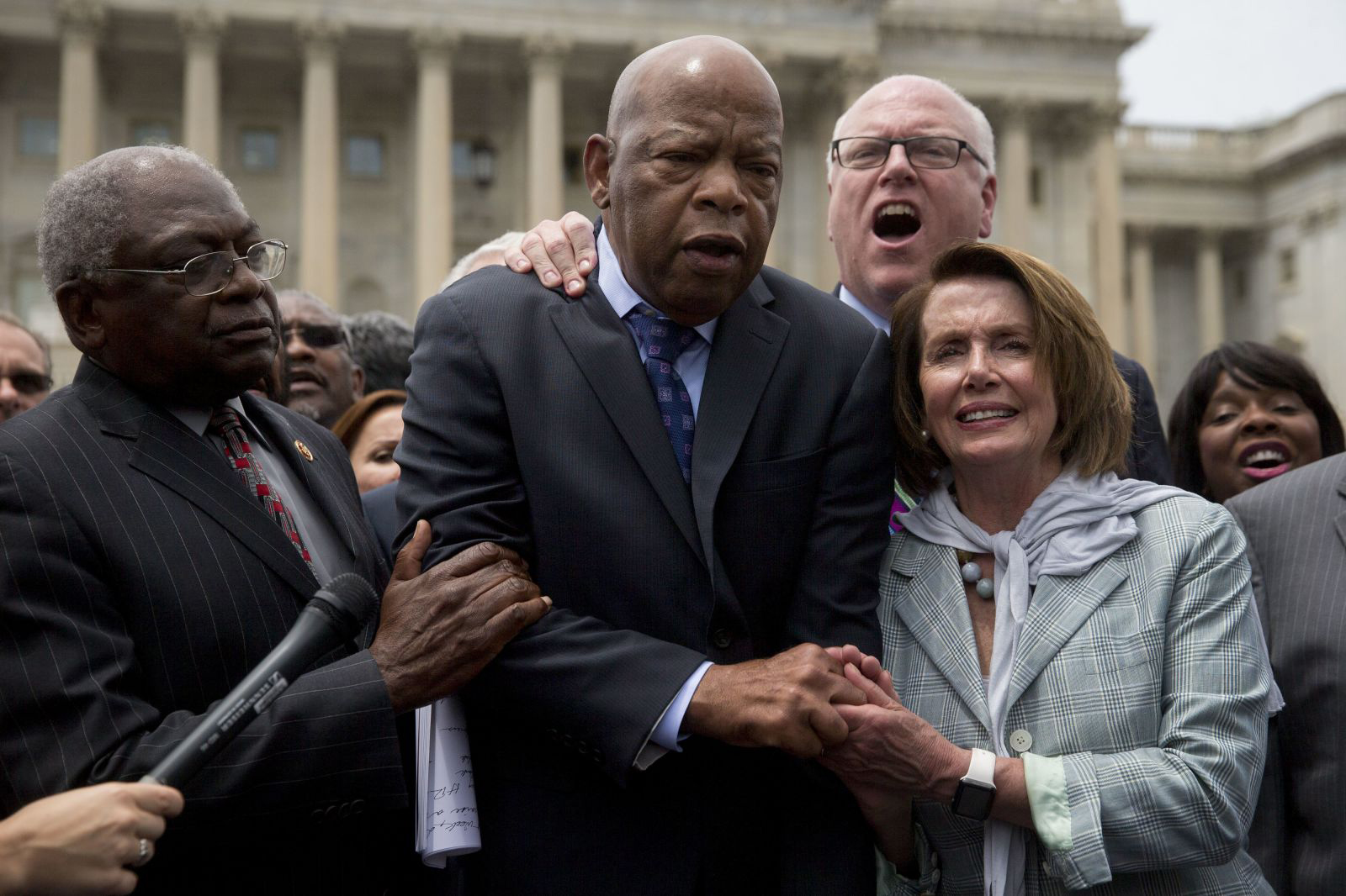 John Lewis is joined by Nancy Pelosi and US Reps. Jim Clyburn and Joe Crowley as Democrats sing a song outside the US Capitol in June 2016.