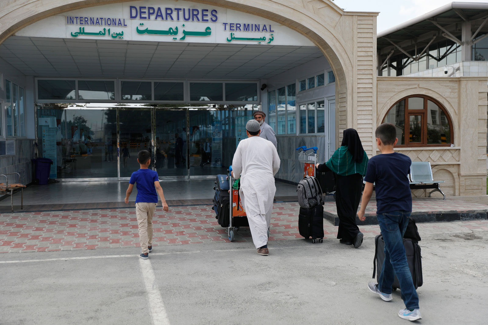Passengers enter the departures terminal of Hamid Karzai International Airport, in Kabul, Afghanistan, on August 14.