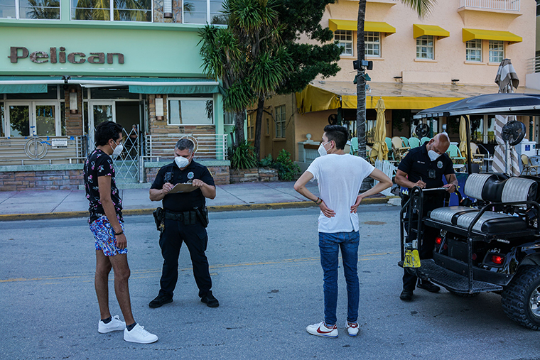 Miami Beach Police officers issue a ticket to visitors for not wearing facemasks on Ocean Drive in Miami Beach, Florida on August 27.