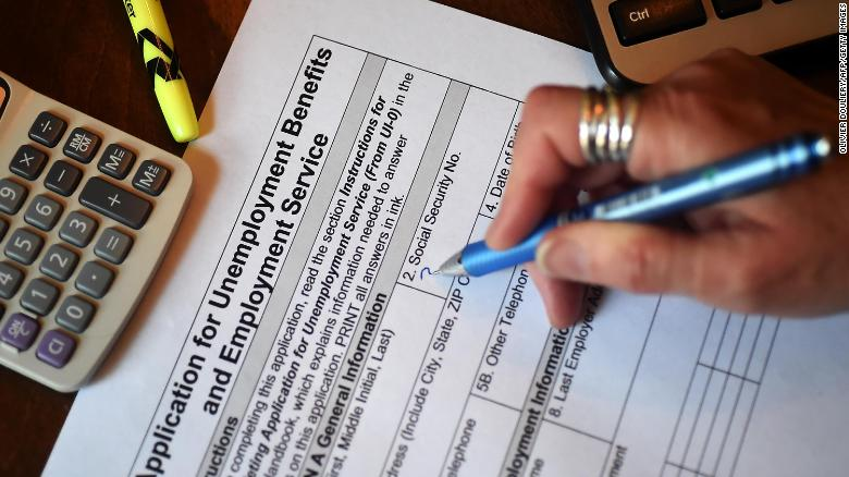 In this photo illustration, a person files an application for unemployment benefits.