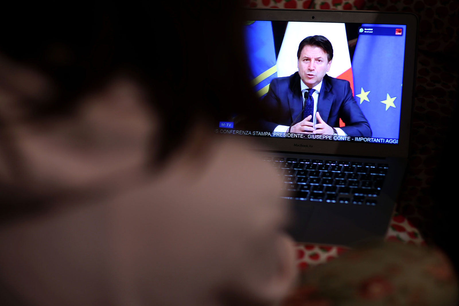A girl watches Italian Prime Minister Giuseppe Conte announce the shut down of all non-essential production activities on March 21, in Rome, Italy.