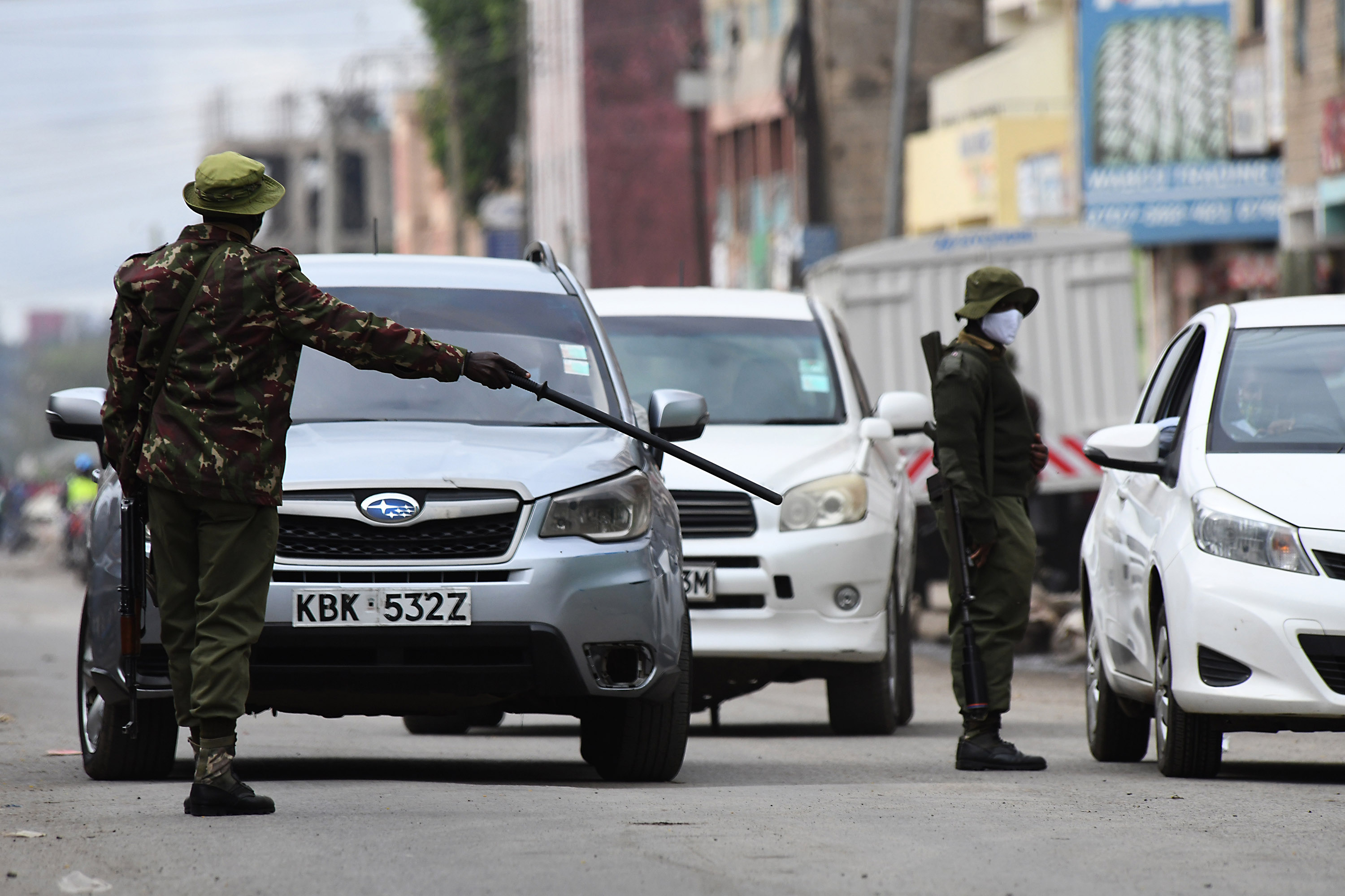 Kenyan police officers inspects drivers at a checkpoint following a partial lockdown in two COVID-19 hotspots of Eastleigh in Nairobi and Mombasa City in Kenya, on May 7.