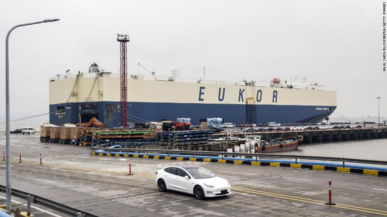 A new Tesla rolls off a ship in the port of Shanghai.