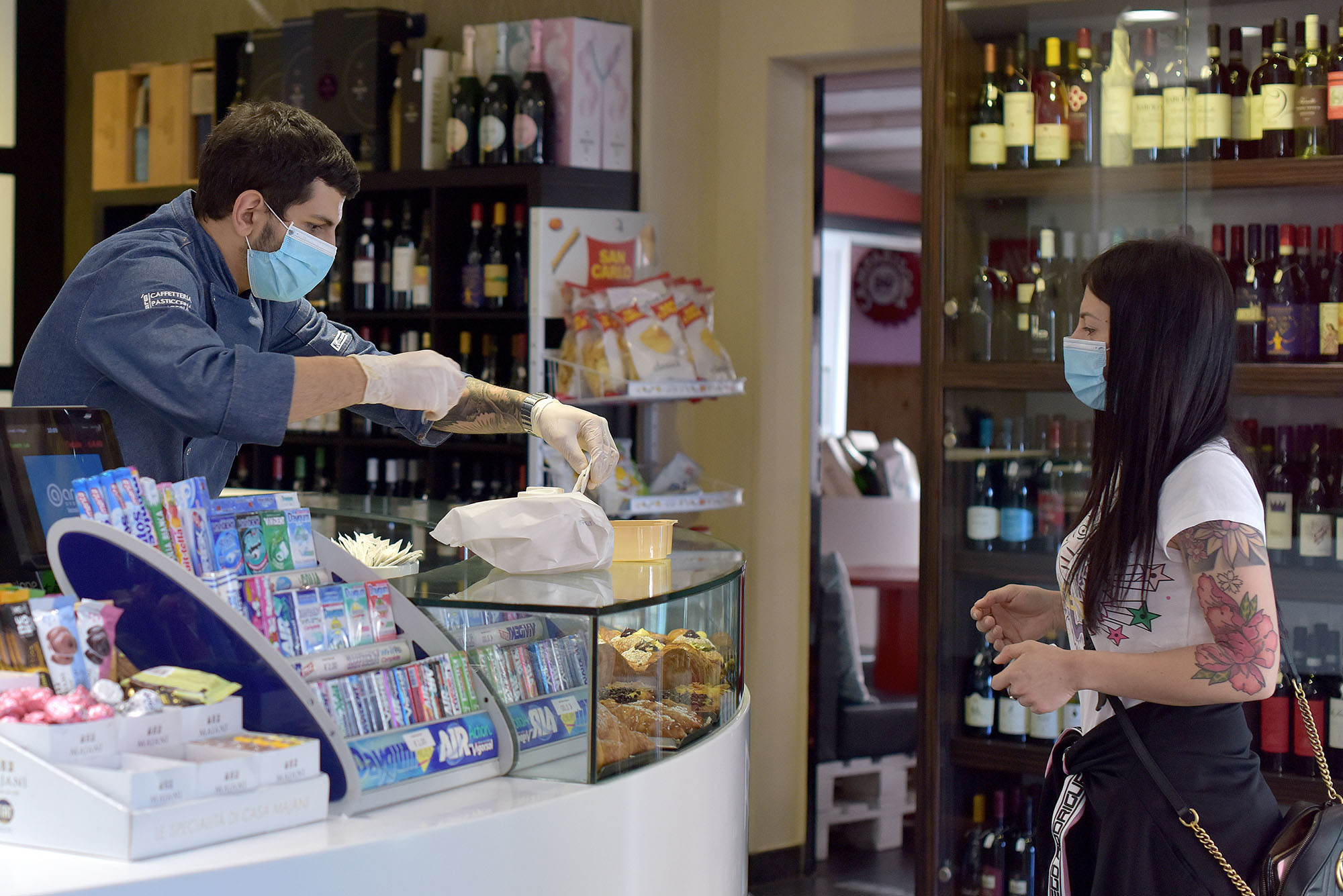 Cafe clerks prepare coffee and cappuccinos for customers waiting to take out in Rome, Italy, on May 4.
