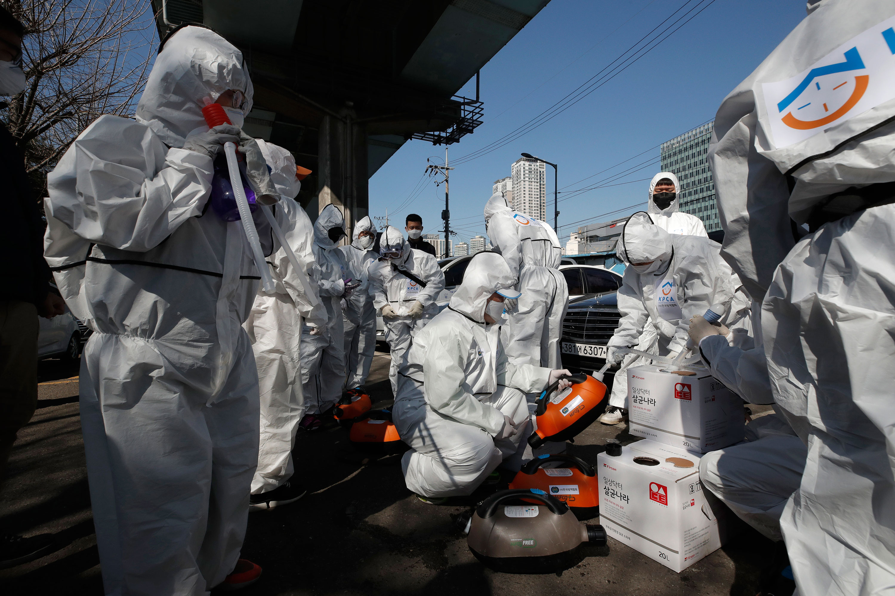 Workers prepare to spray disinfectant as a precaution against coronavirus in Seoul, South Korea on March 16.