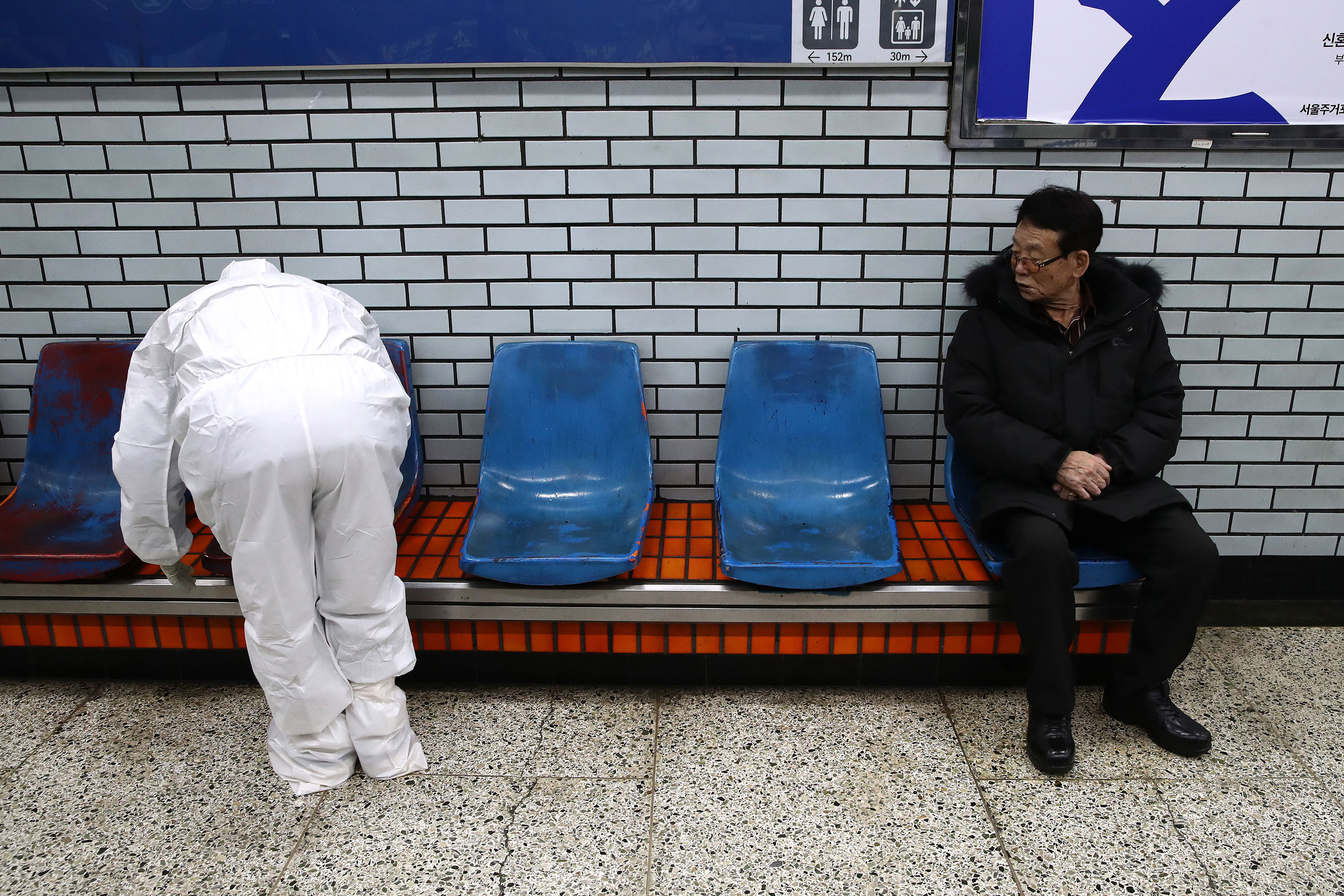 An official in protective clothing sprays disinfectant in a subway station in Seoul.
