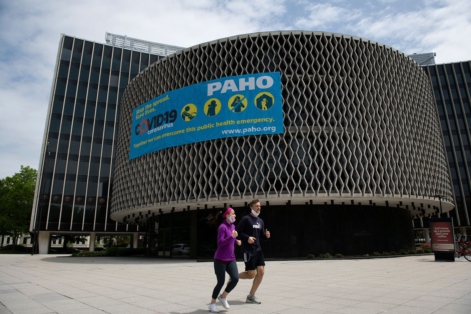 Joggers run by the Pan American Health Organization building in Washington, DC, on May 21.