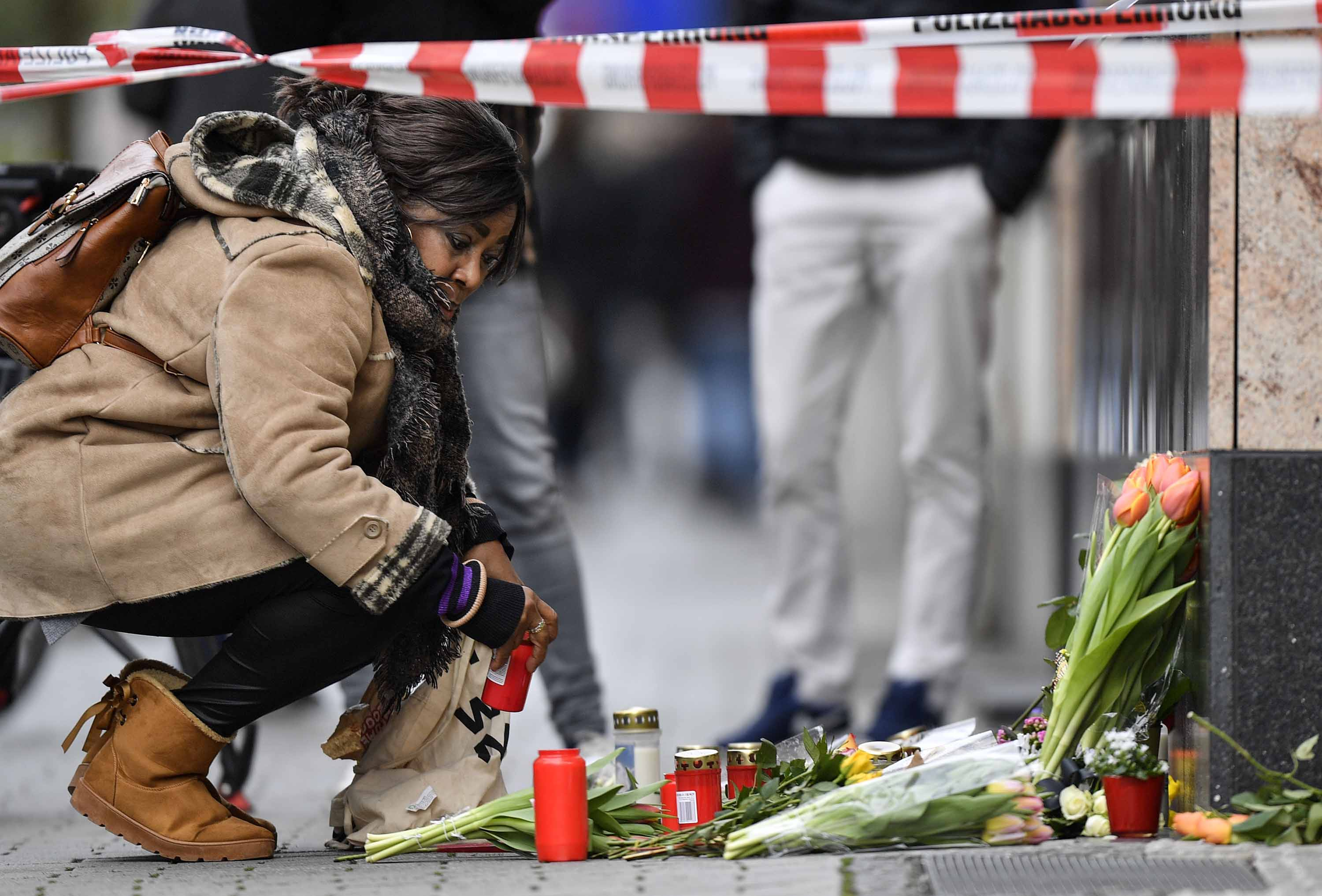 A woman places a candle at a makeshift victims' memorial near the scene of one of the shootings in Hanau.