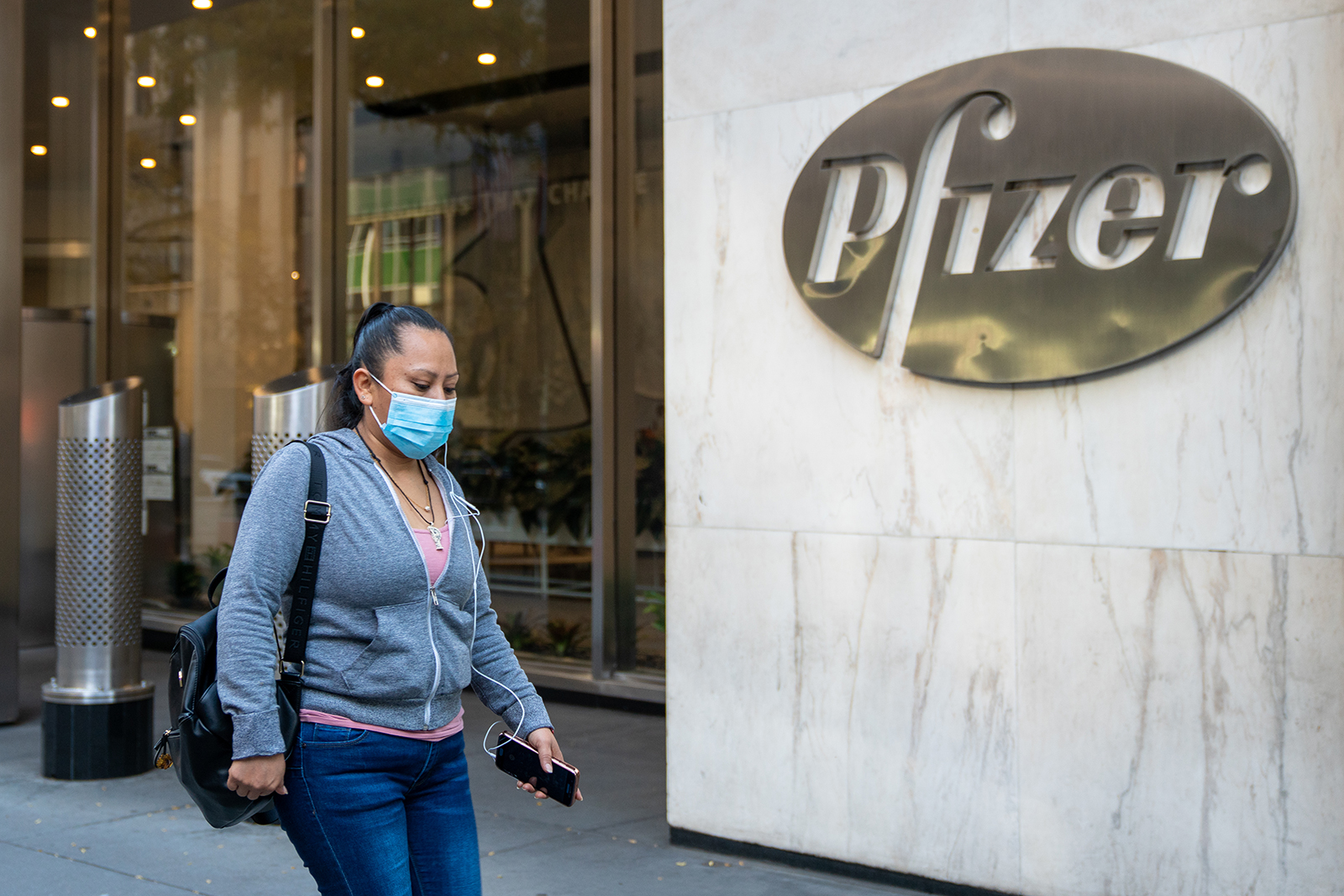 People walk by the Pfizer headquarters on Nov. 9, in New York City.