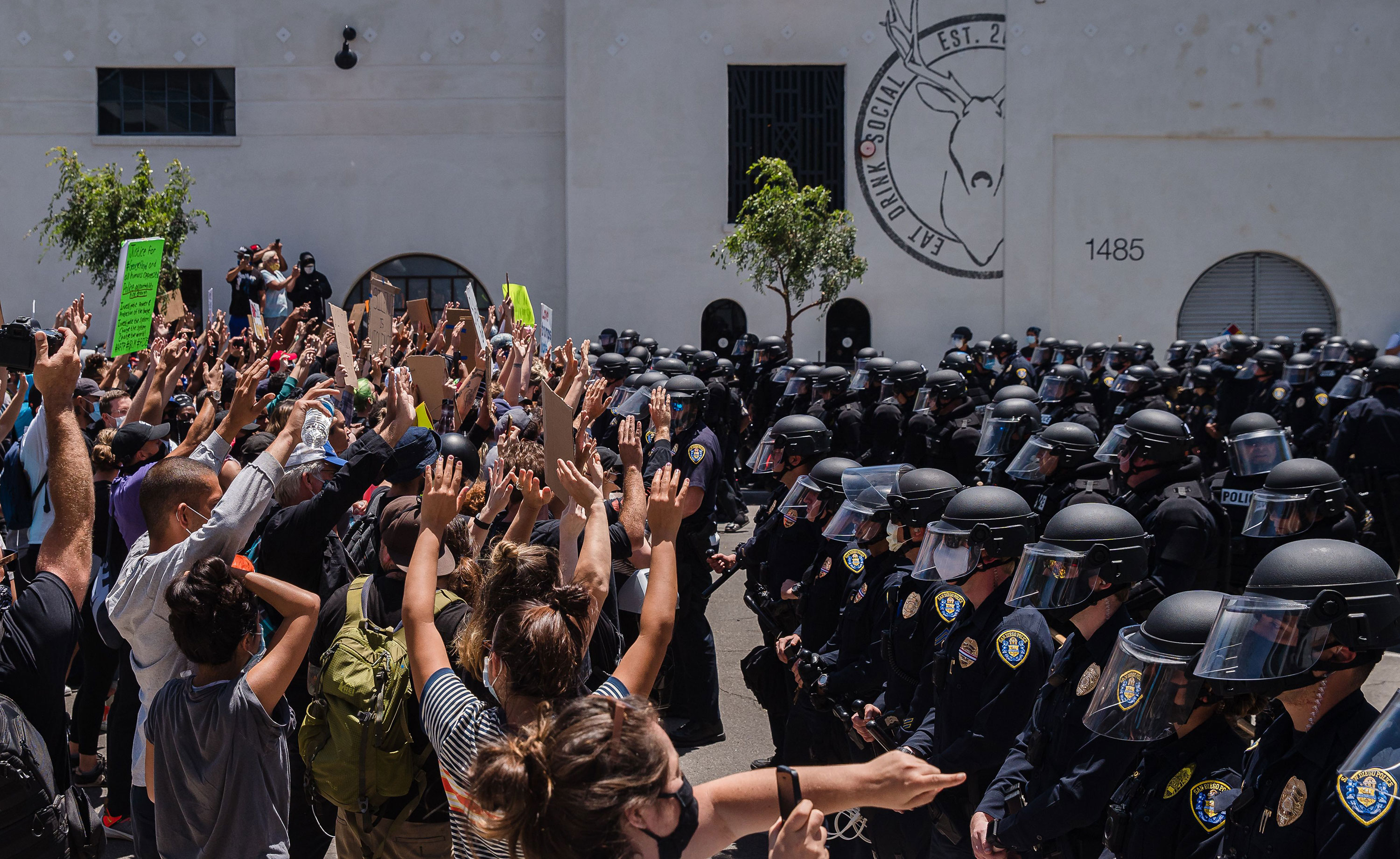Demonstrators gather in front of police officers in downtown San Diego, California, on May 31.