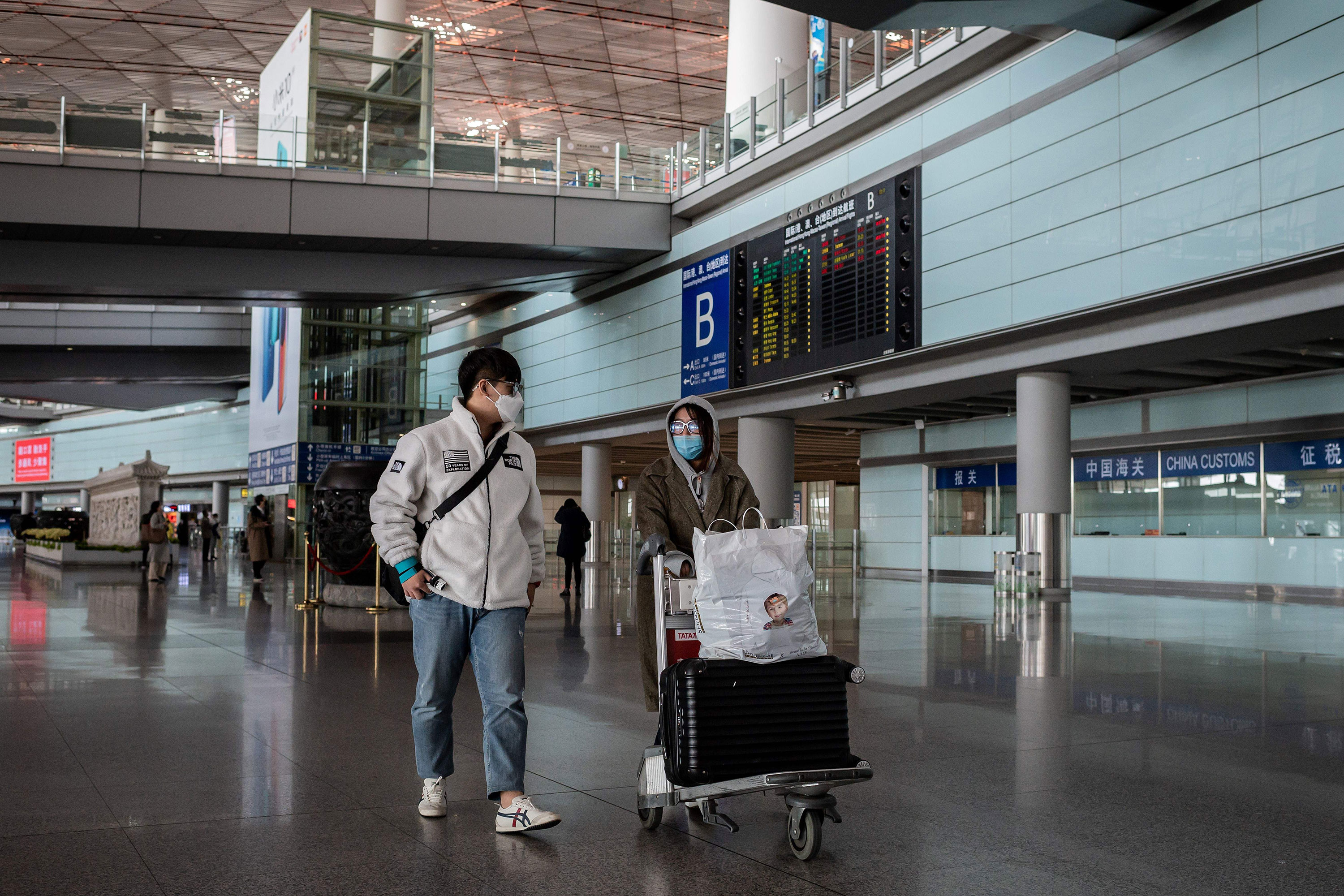 Passengers walk through a nearly empty arrivals area at Beijing Capital Airport in Beijing on March 16.