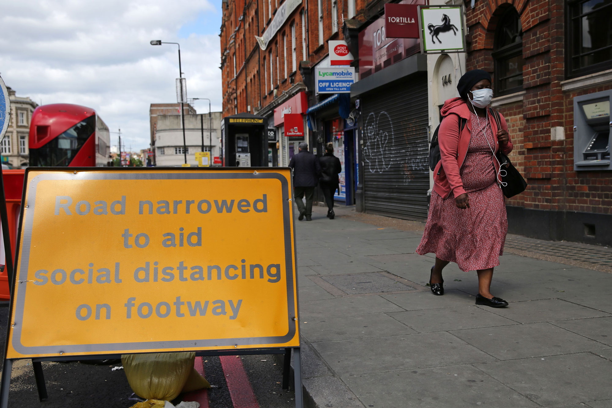 A sign is pictured explaining that the road has been narrowed to aid social distancing when using Camden High Street in central London on May 11.