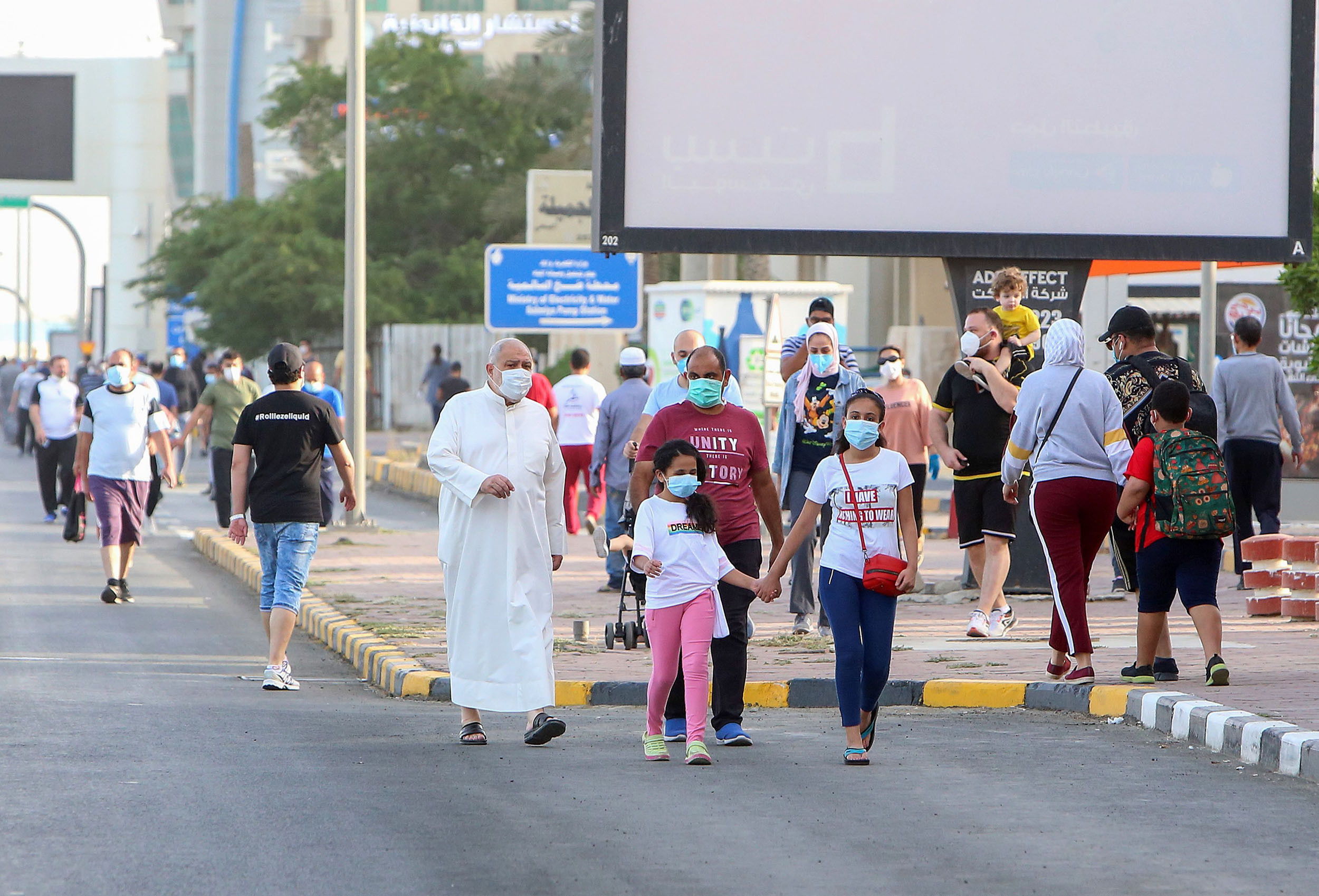 Residents walk in a neighborhood of Kuwait City, on May 12, as authorities allowed people to exercise for two hours under a nationwide lockdown due to the COVID-19 pandemic.
