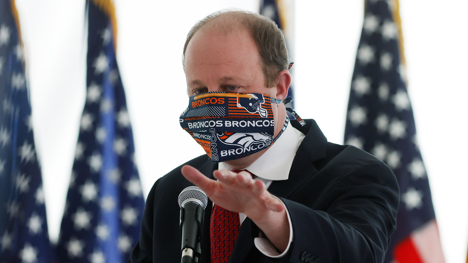 Colorado Governor Jared Polis wears a face mask as he answers a question during a news conference to update the state's efforts to stop the spread of the new coronavirus in Denver, Colorado on April 22.