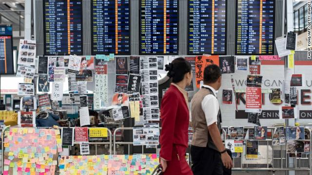 Flight attendants walk past a display board covered with memos and posters at Hong Kong's international airport on Tuesday.