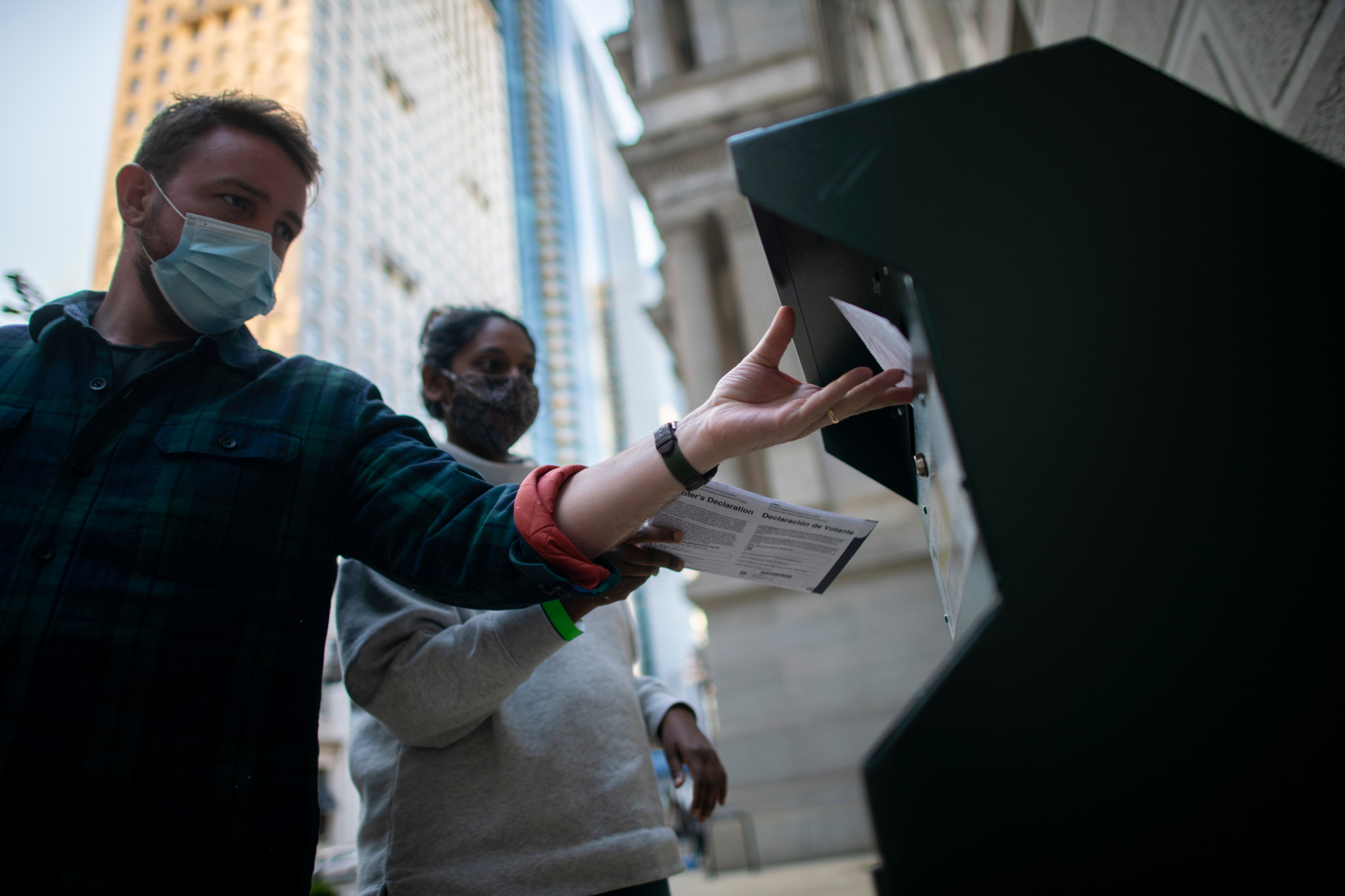Voters cast their early voting ballot at drop box outside of City Hall on October 17 in Philadelphia, Pennsylvania.
