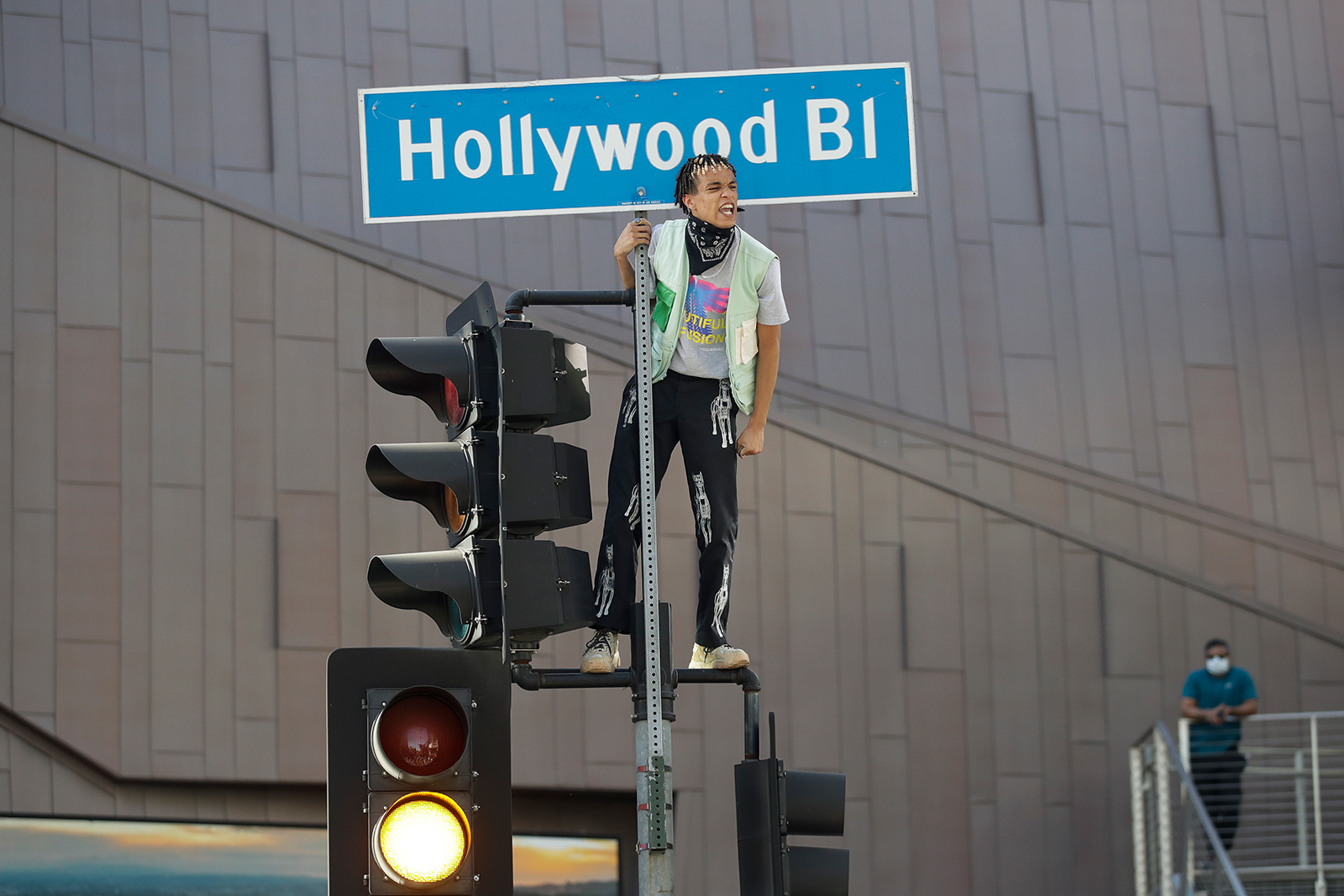 A demonstrator shouts slogans after climbing on a traffic light on June 7, in the Hollywood area of Los Angeles.