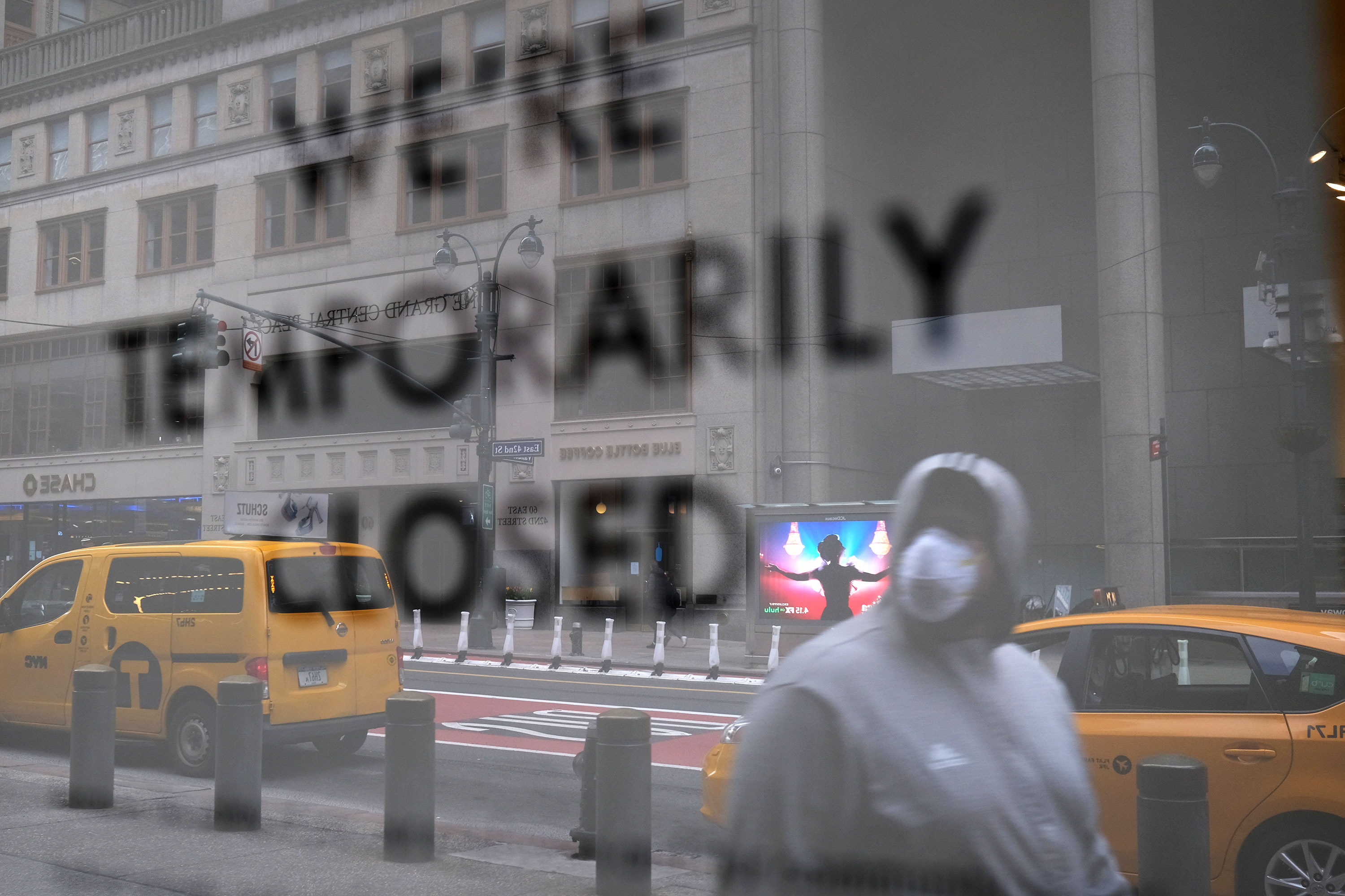 A pedestrian walks past a closed business, in Manhattan, New York, on April 10.