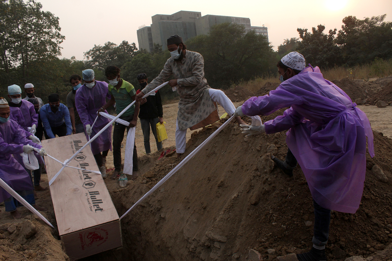 Family members in personal protective equipment (PPE) kits along with other relatives perform the burial of a person who died of Covid-19, at Jadid Qabristan Ahle- Islam graveyard, in New Delhi, on November 12.