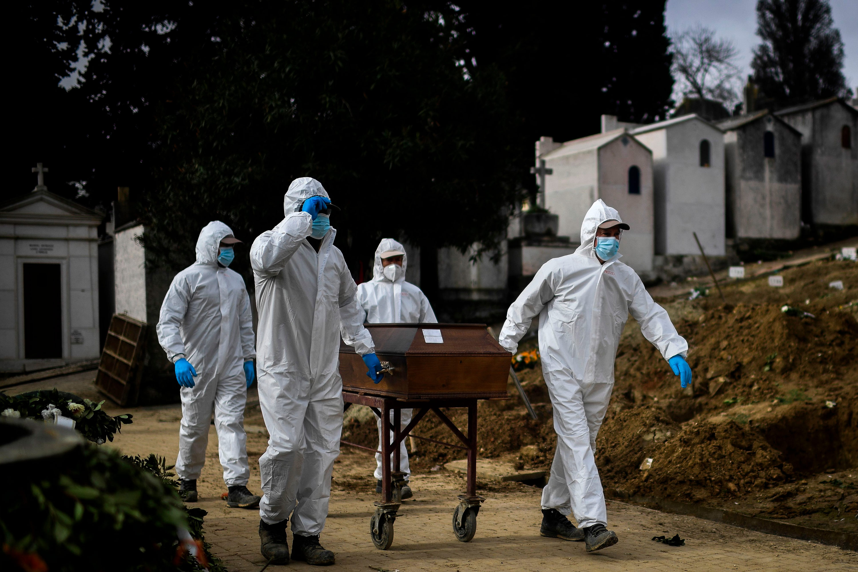 Grave diggers push the coffin of a Covid-19 victim before a burial at the Alto de Sao Joao cemetery in Lisbon, Portugal, on February 18.