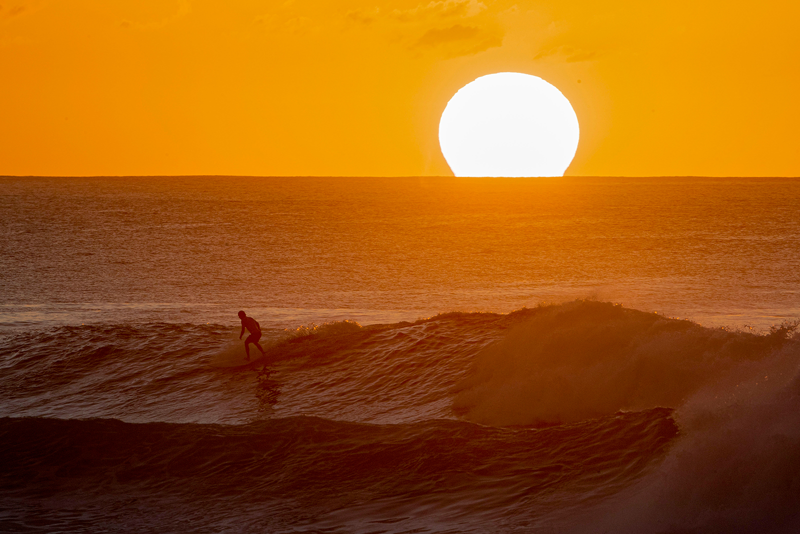 A surfer rides a wave as the sun sets on the horizon on the north shore of Oahu in Hawaii on January 28.