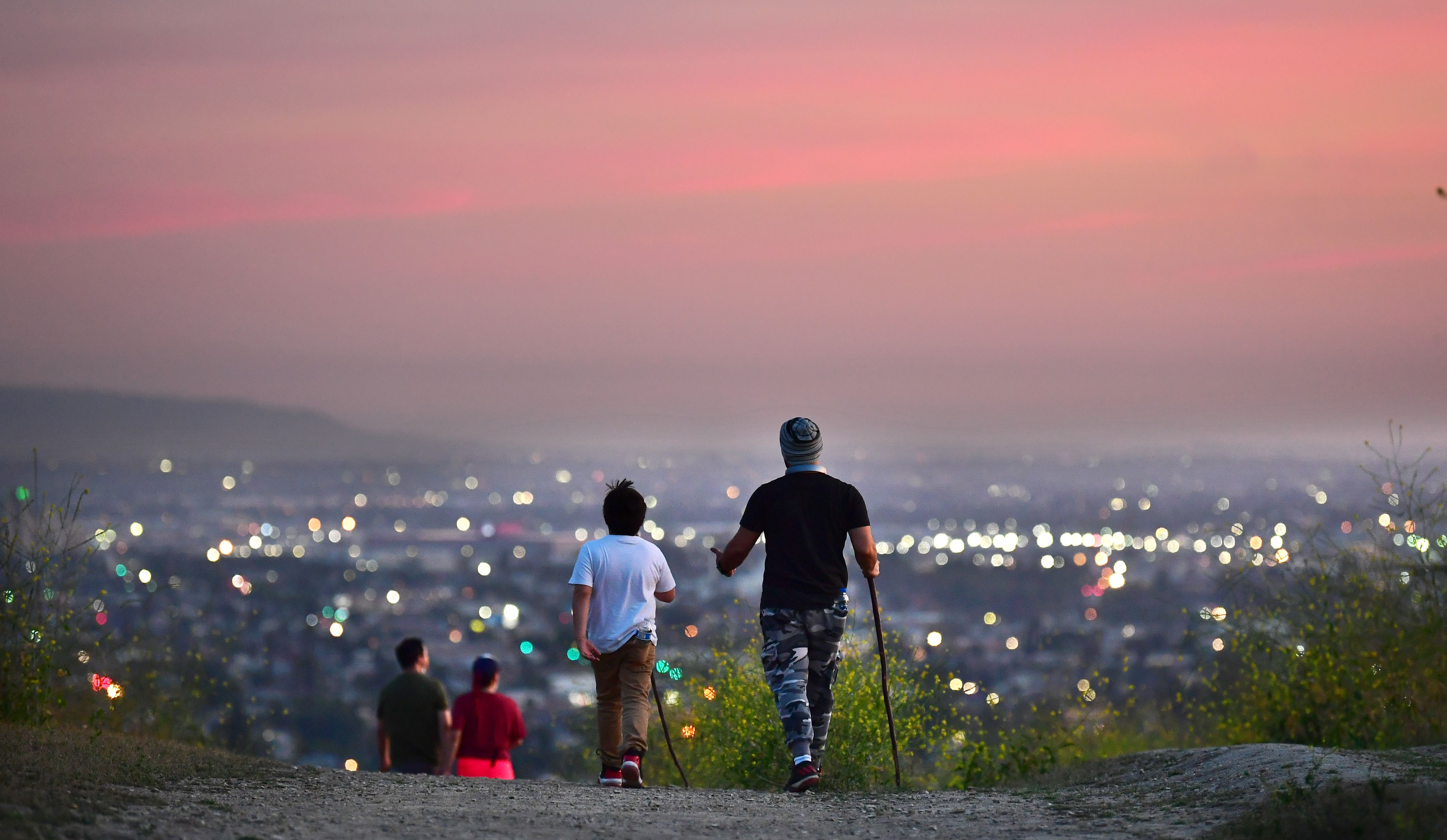 People hike on a trail at dusk in Los Angeles on May 7.
