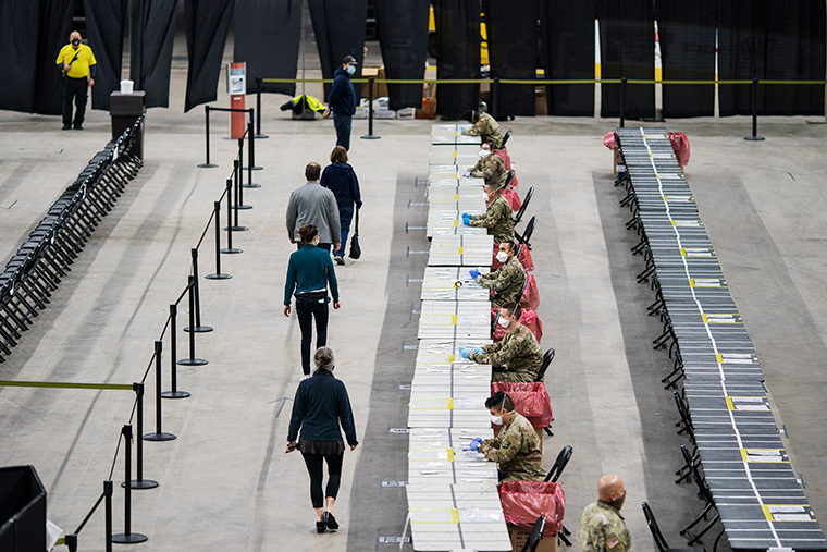 The first patients walk onto the floor of the Dunkin' Donuts Center as a new COVID-19 rapid testing site operated by the Rhode Island Army National Guard opens in Providence, Rhode Island, on Tuesday, December 1.