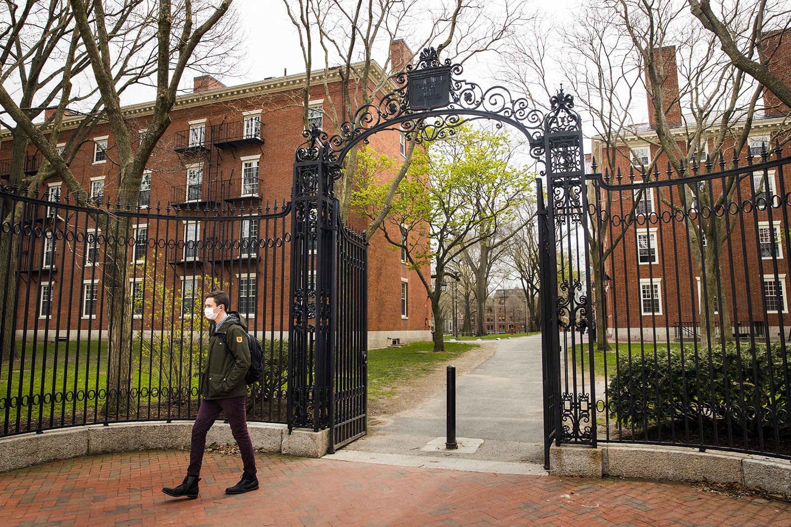 A pedestrian wearing a protective mask exits Harvard Yard on the closed Harvard University campus in Cambridge, Massachusetts, on April 20.