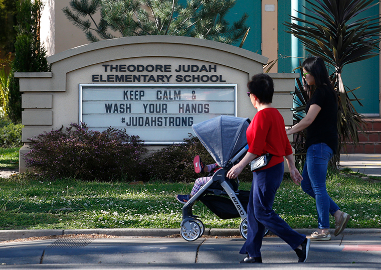 A reminder for people to wash their hands is displayed on a sign outside Theodore Judah Elementary School in Sacramento, California on April 1.