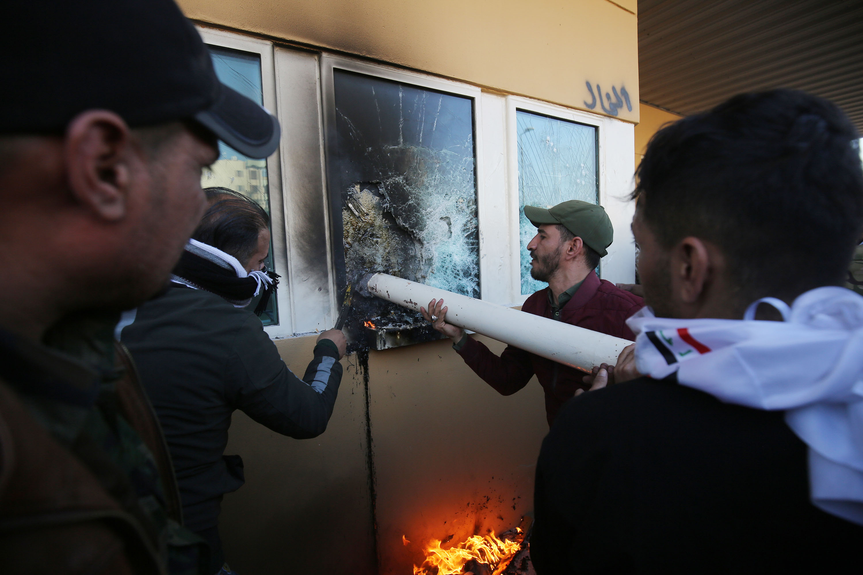 Protesters use a pipe to break the bullet-proof glass windows at the US embassy in Baghdad.